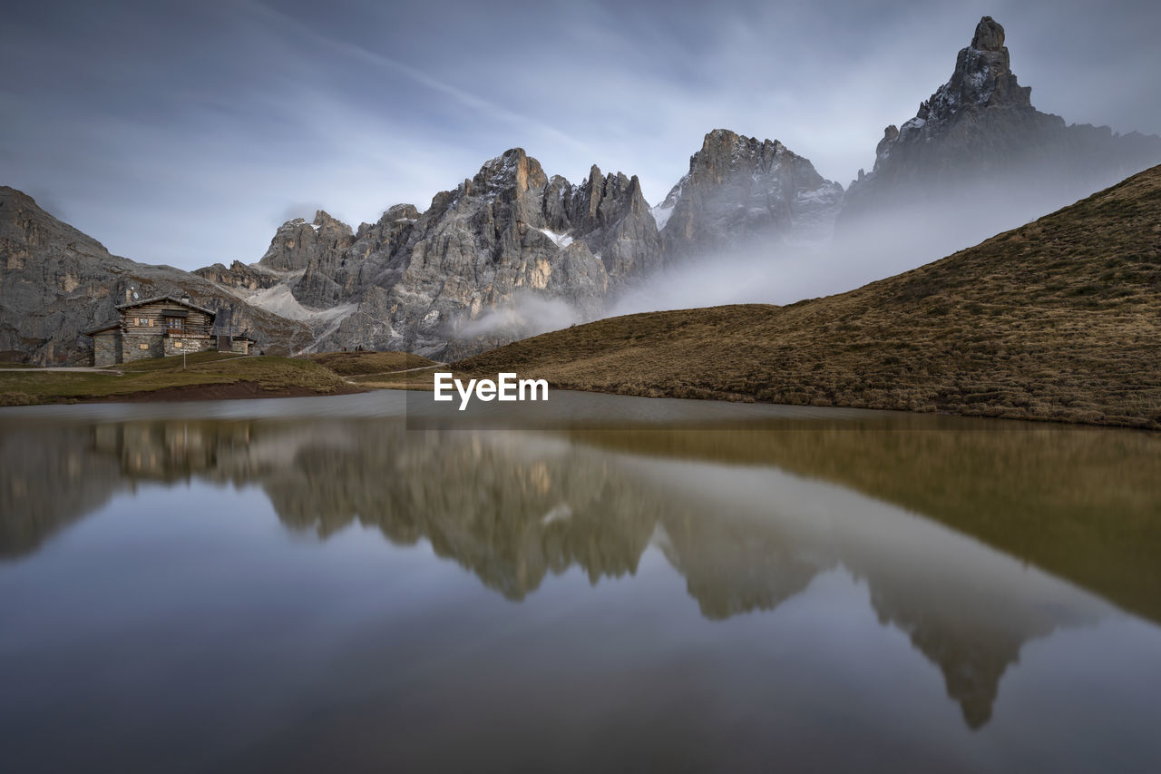 Scenic view of lake baita segantini and snowcapped mountains against sky