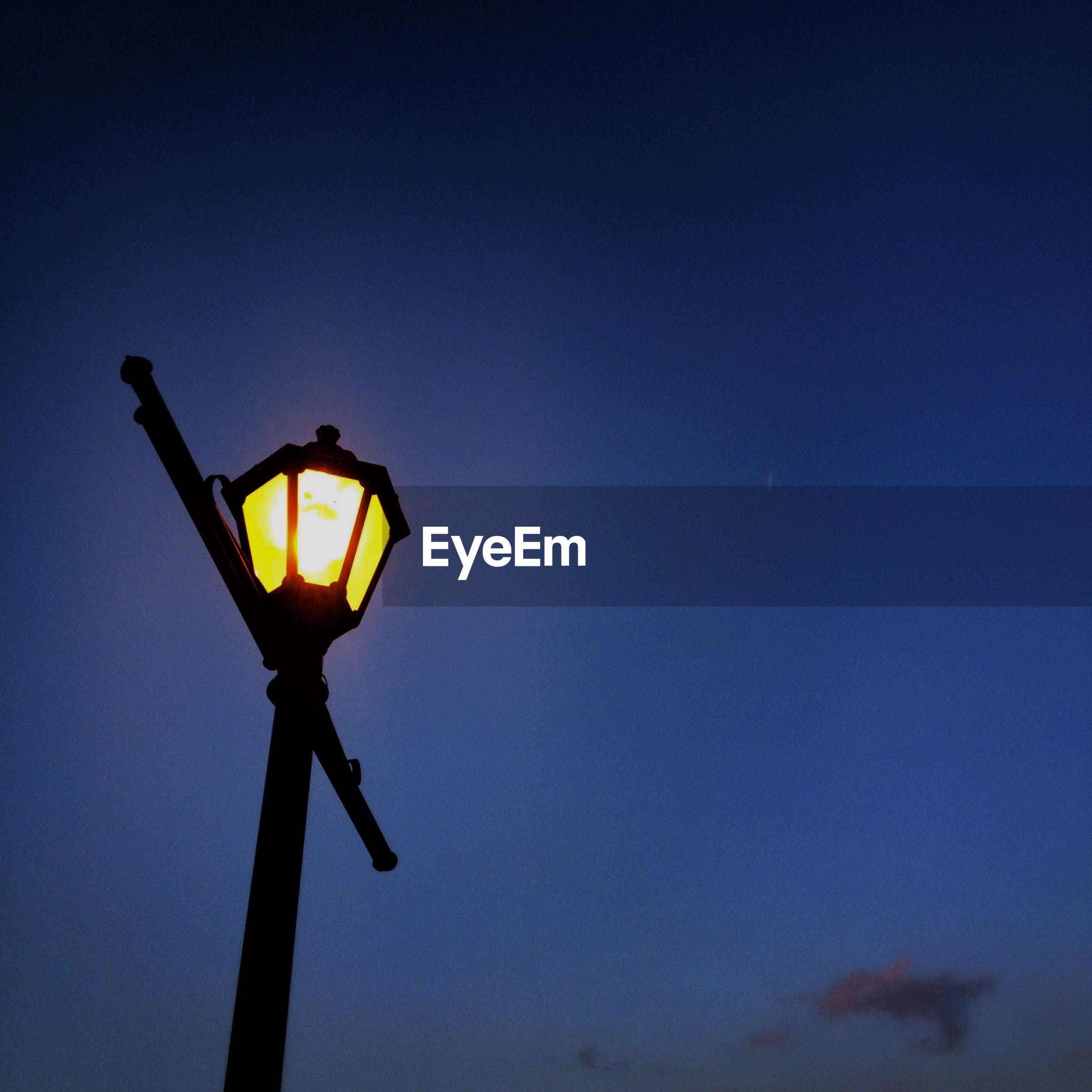 Illuminated lantern against sky