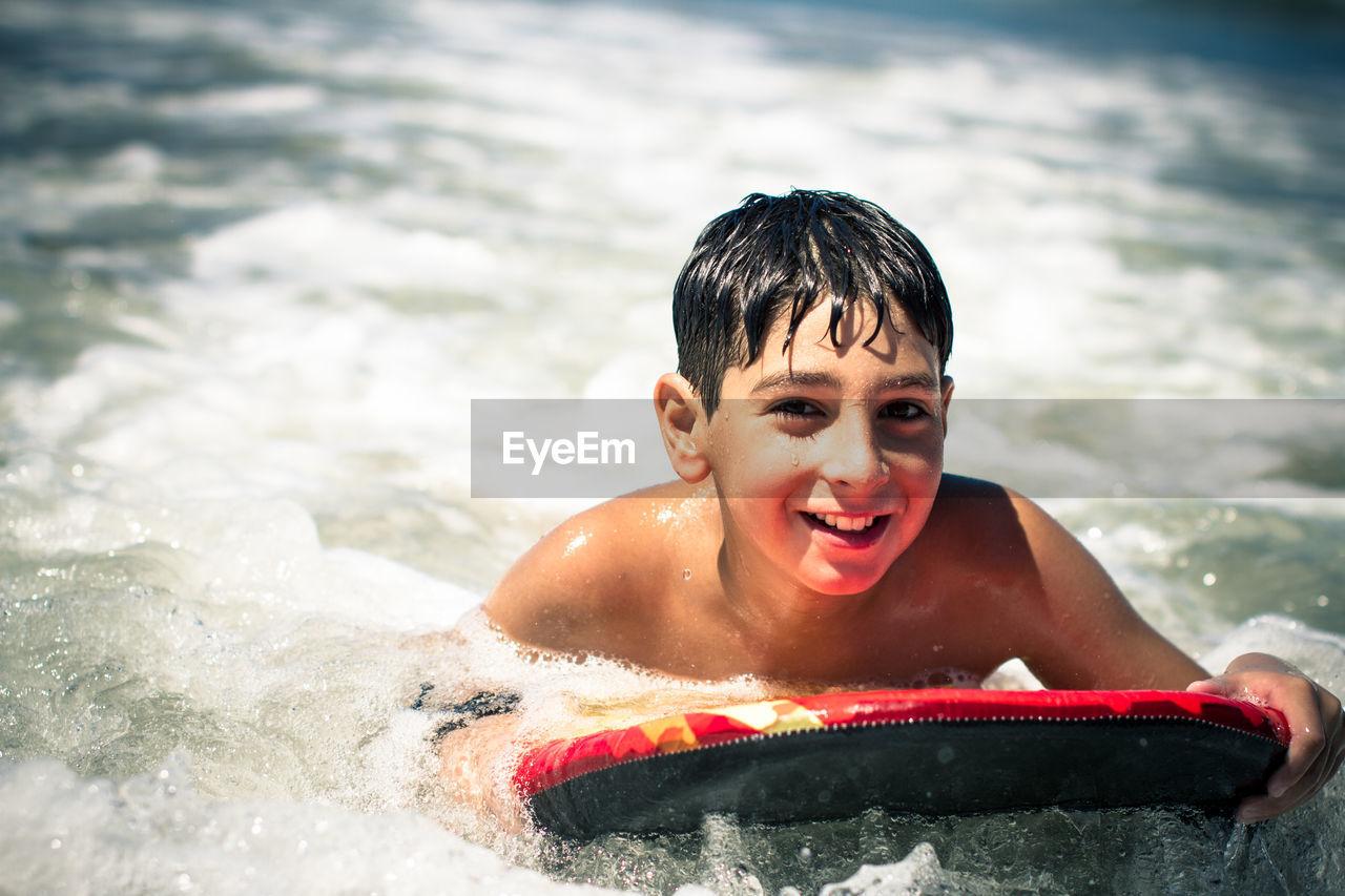 Portrait Of Boy Bodysurfing In Sea