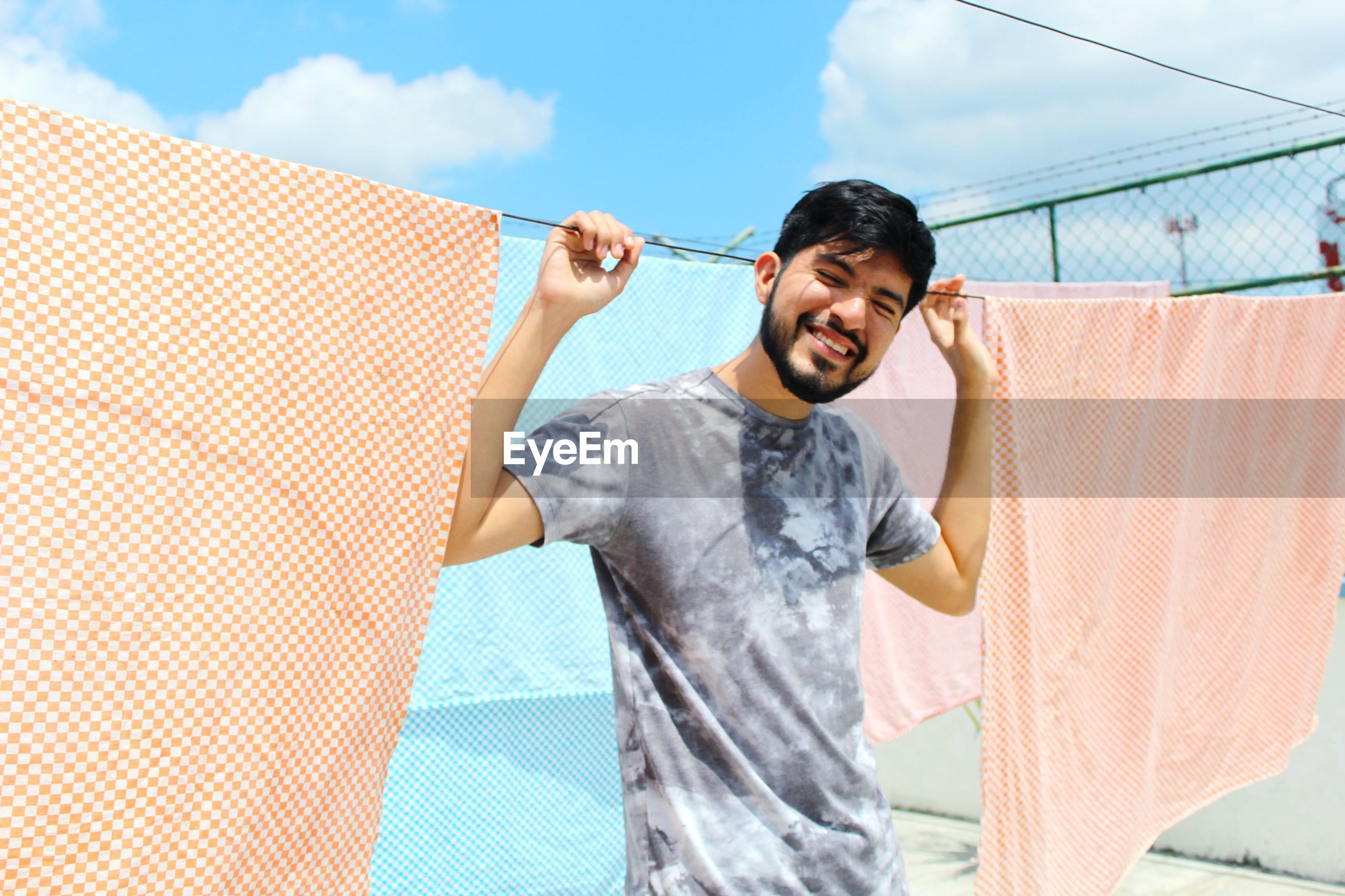 Smiling man standing by clothesline against sky
