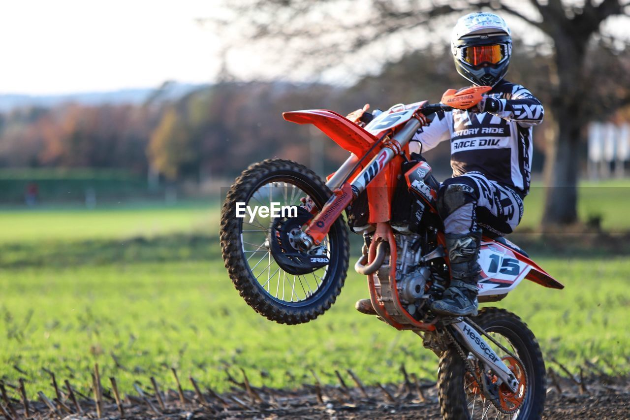 transportation, mode of transportation, land vehicle, helmet, motorcycle, field, headwear, land, motocross, sport, day, focus on foreground, nature, ride, one person, riding, extreme sports, sports helmet, biker, sports clothing, crash helmet, outdoors