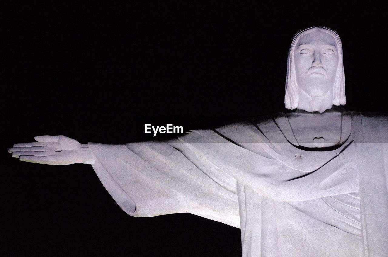 Close-up of jesus christ statue against black background