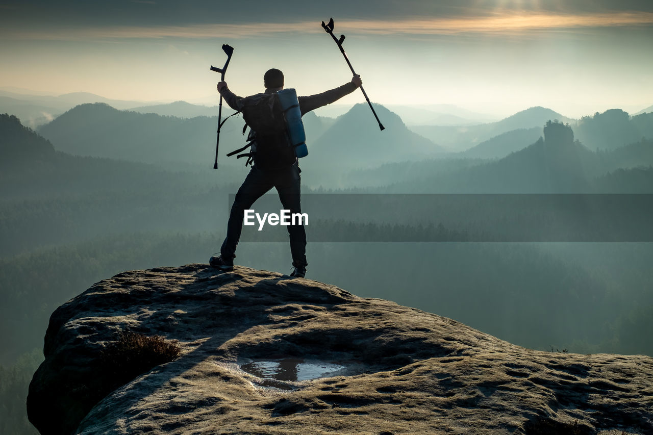 Happy man with arms outstretched holding crutches at mountain valley in sunset. personal motivation