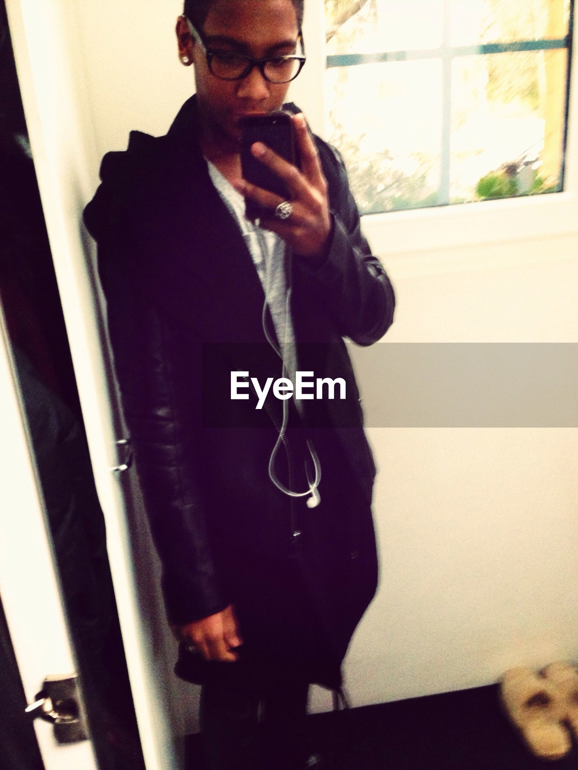 indoors, young adult, lifestyles, person, young men, casual clothing, leisure activity, standing, front view, wall - building feature, full length, three quarter length, side view, holding, looking at camera, reflection, mirror