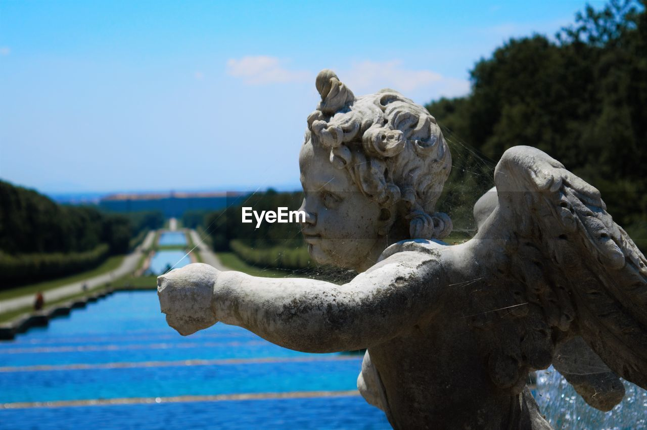 Close-Up Of Old Statue By Water Against Sky