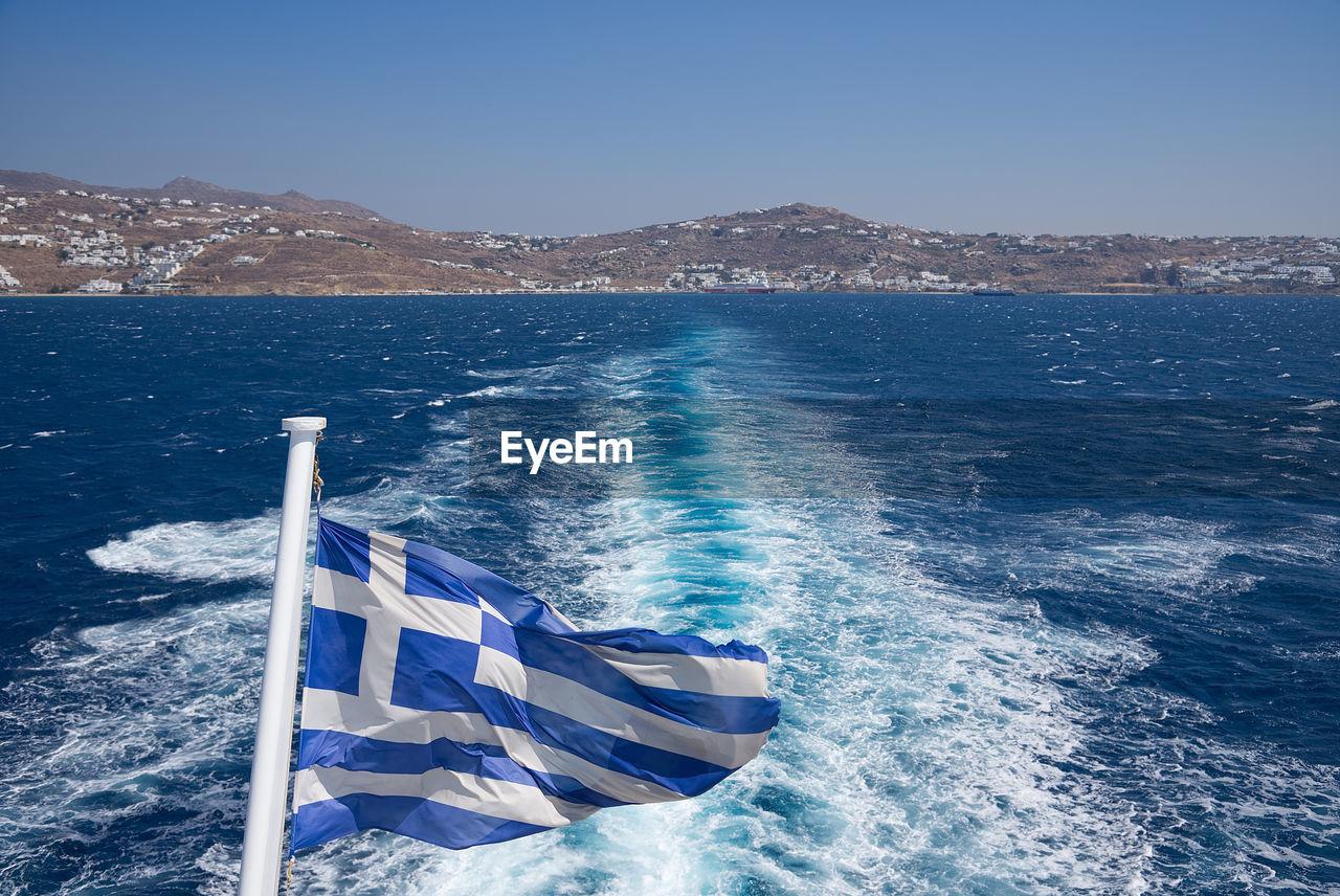 Greek flag against sea on sunny day