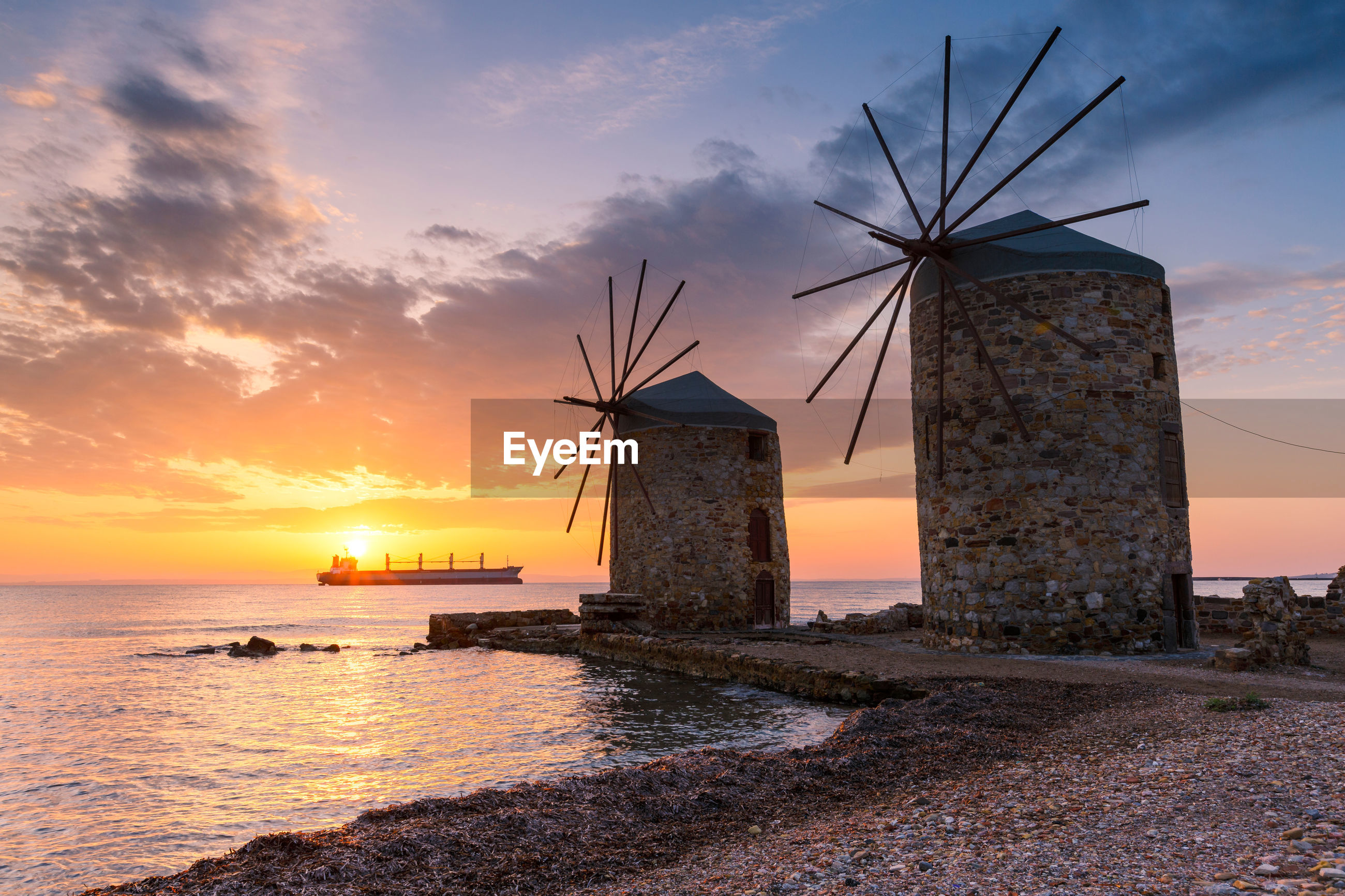 TRADITIONAL WINDMILL BY SEA AGAINST SKY AT SUNSET