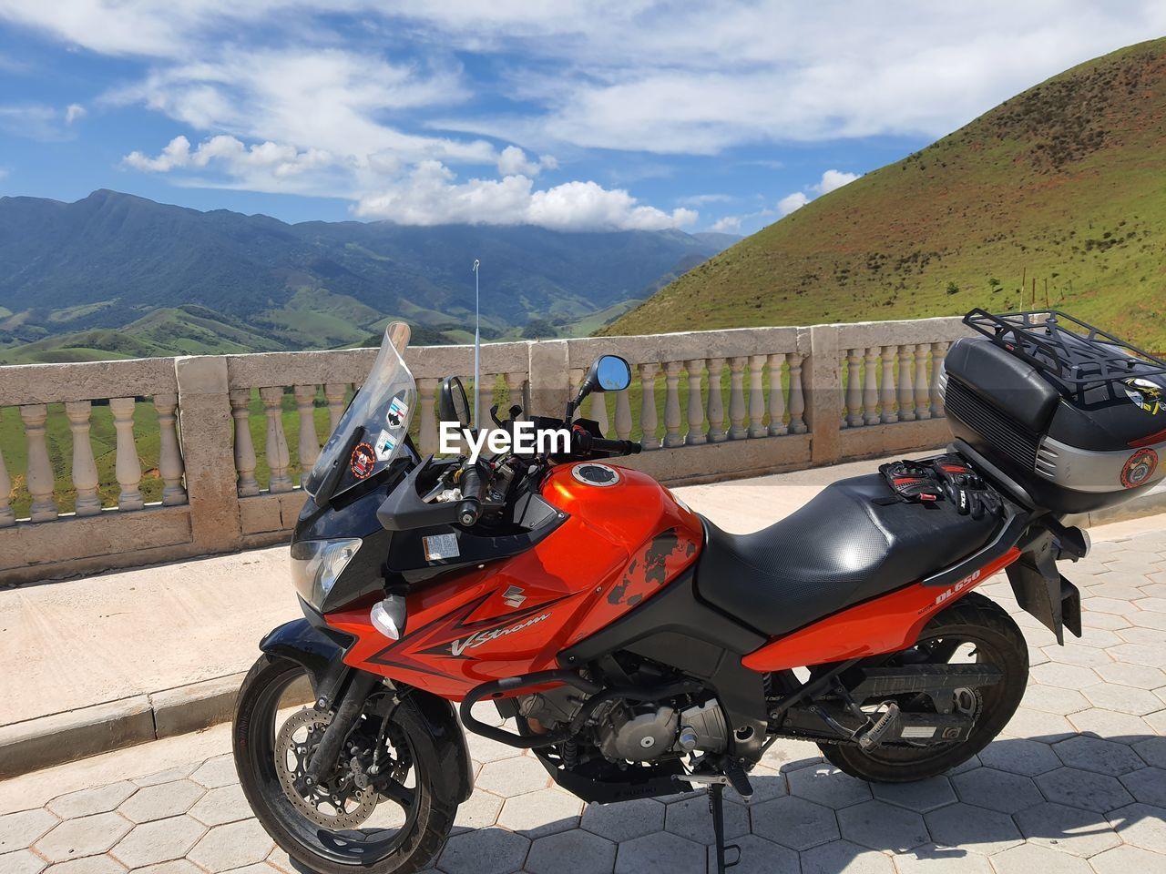MOTOR SCOOTER AGAINST MOUNTAIN RANGE