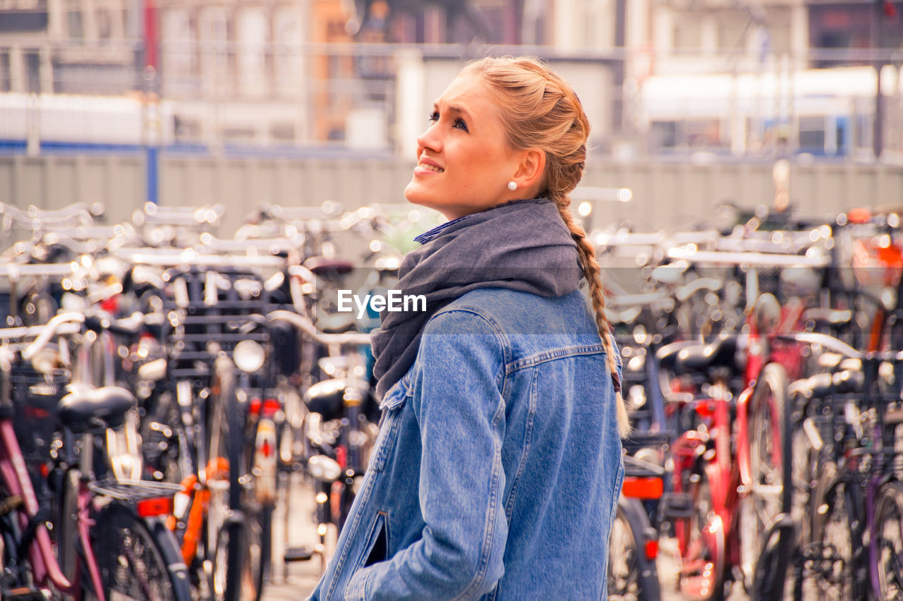 Smiling Young Woman Standing Against Bicycles