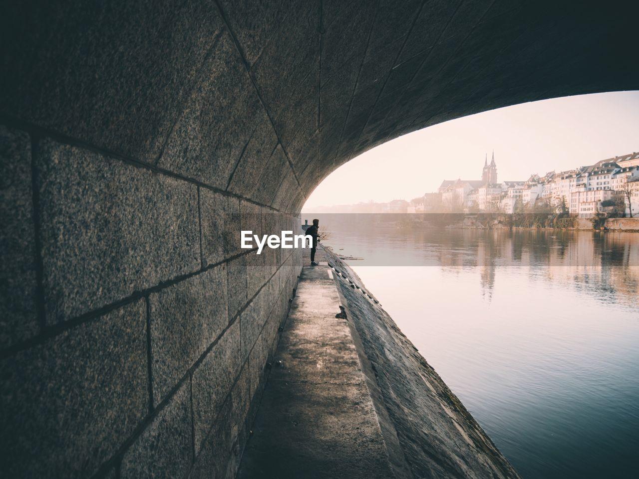 Side view of man under bridge over water