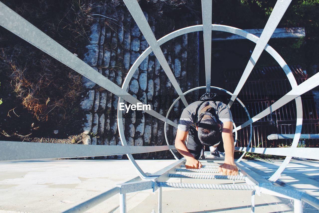 Directly above shot of man climbing ladder