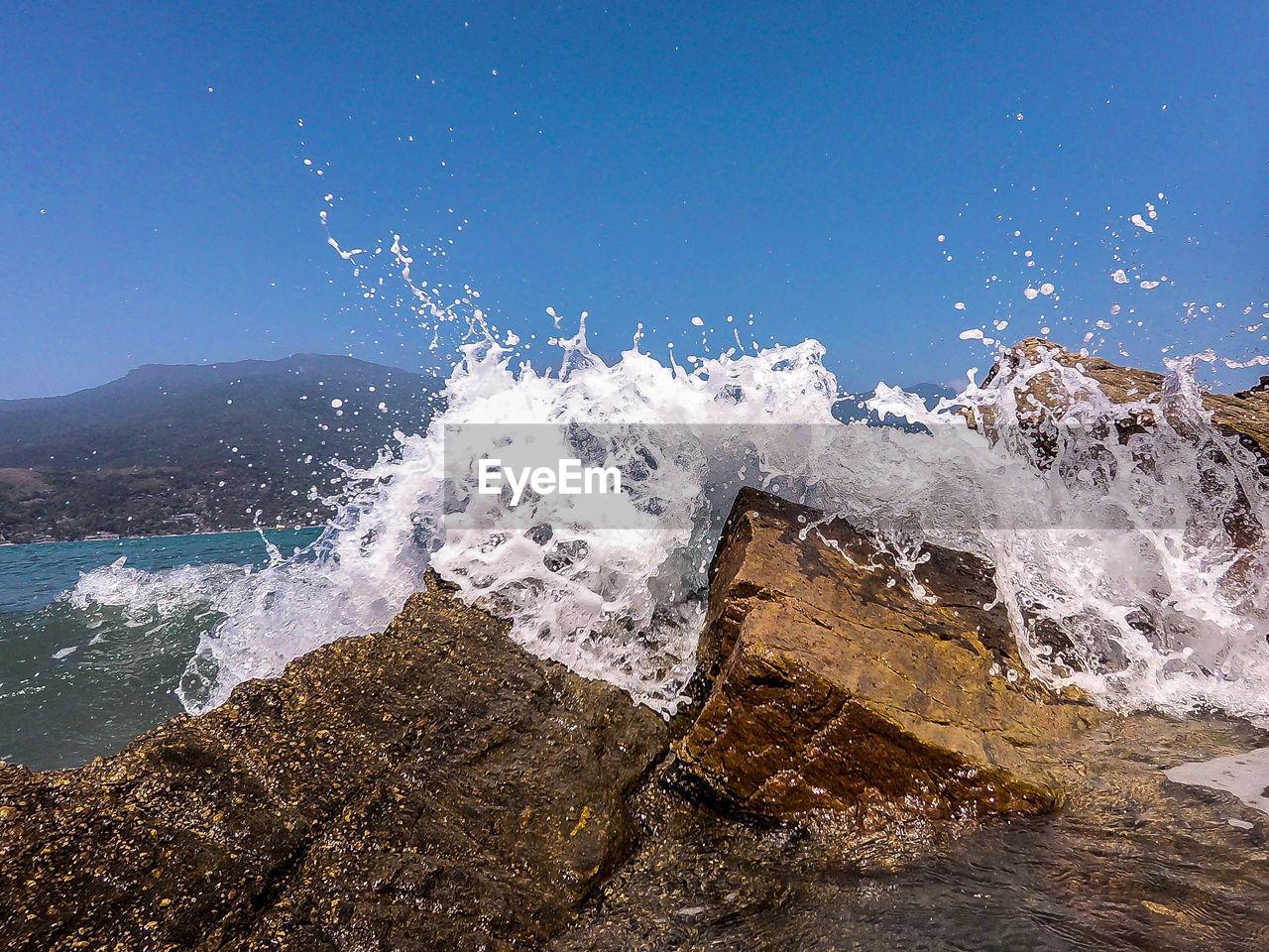 Waves splashing on rocks against clear blue sky