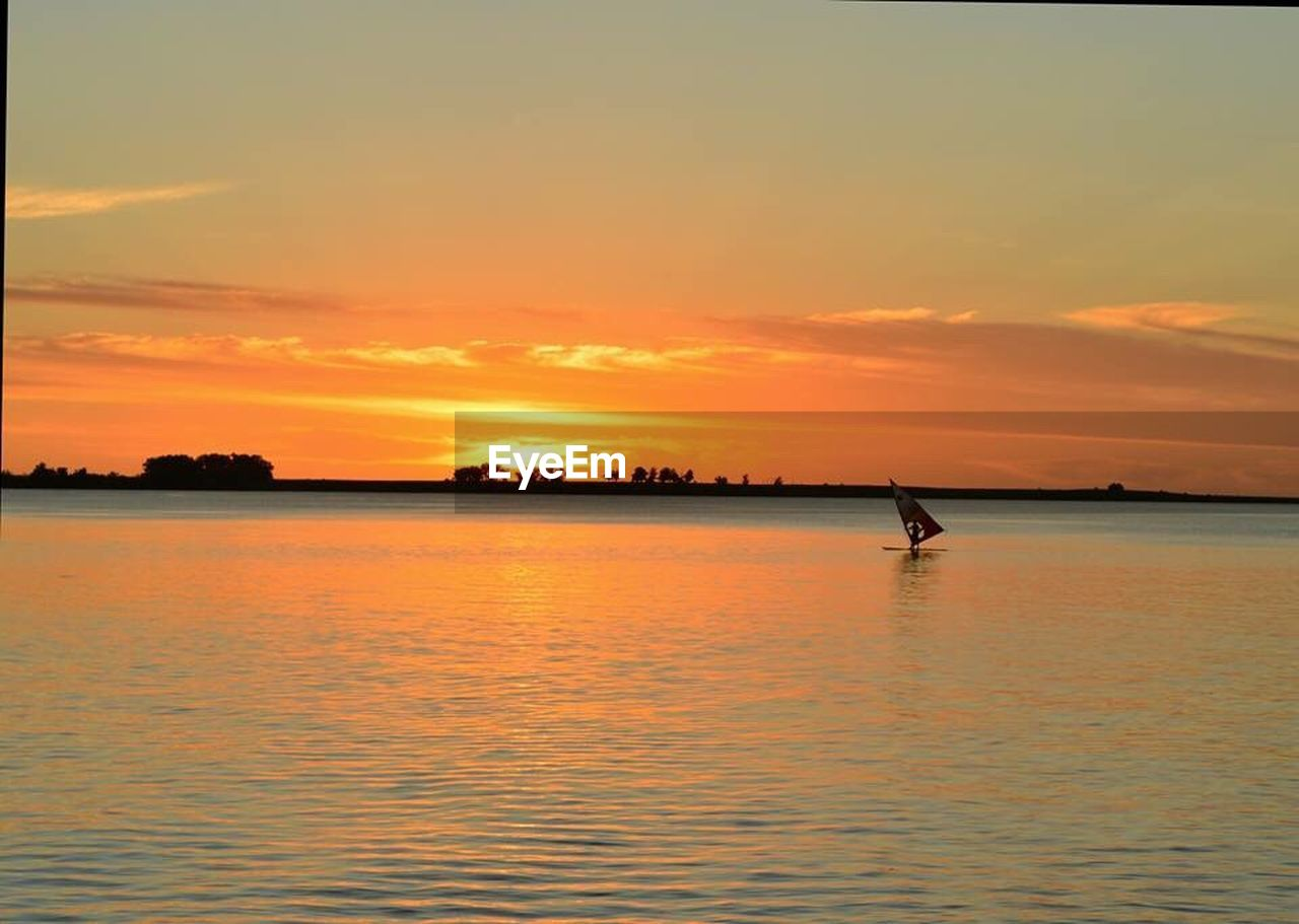 sunset, water, scenics, beauty in nature, nature, silhouette, orange color, sea, tranquil scene, waterfront, tranquility, sky, reflection, idyllic, outdoors, rippled, one person, real people, men, nautical vessel, one man only, day, people
