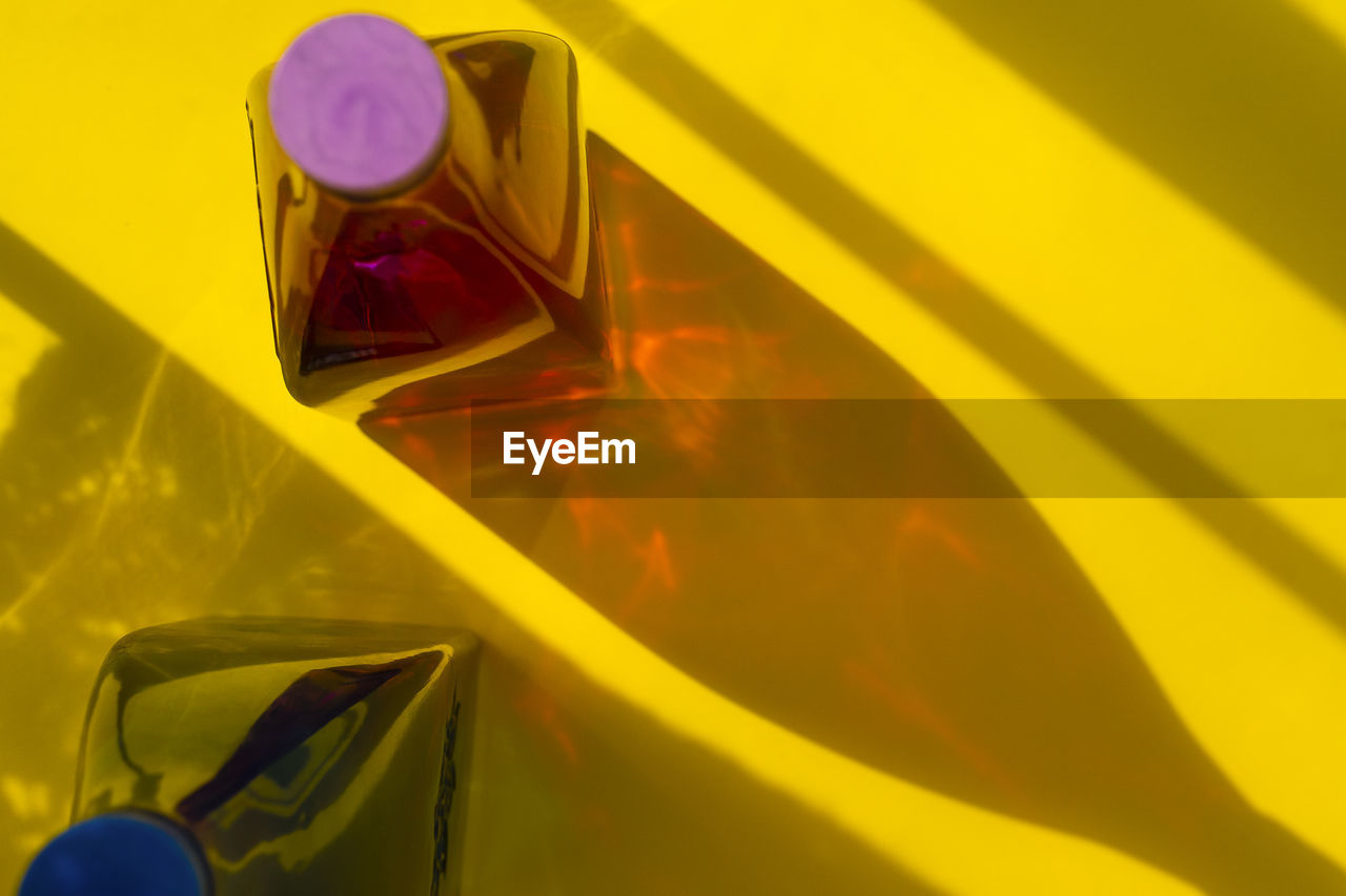 FULL FRAME SHOT OF YELLOW GLASS WITH REFLECTION ON MIRROR