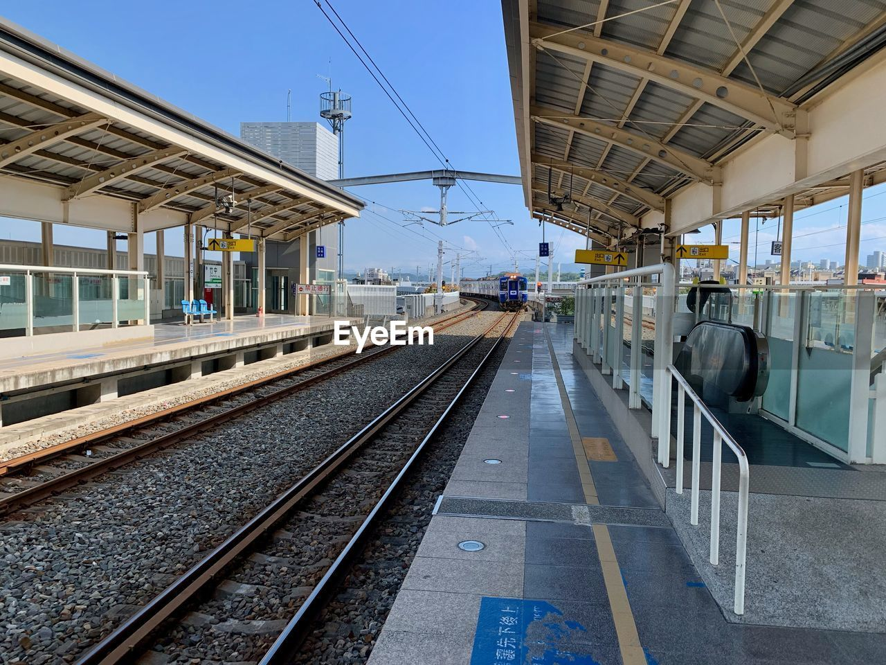 architecture, track, transportation, railroad track, built structure, rail transportation, sky, railroad station platform, building exterior, direction, railroad station, nature, the way forward, mode of transportation, day, travel, public transportation, diminishing perspective, outdoors, cable, no people, electricity, station, power supply, long