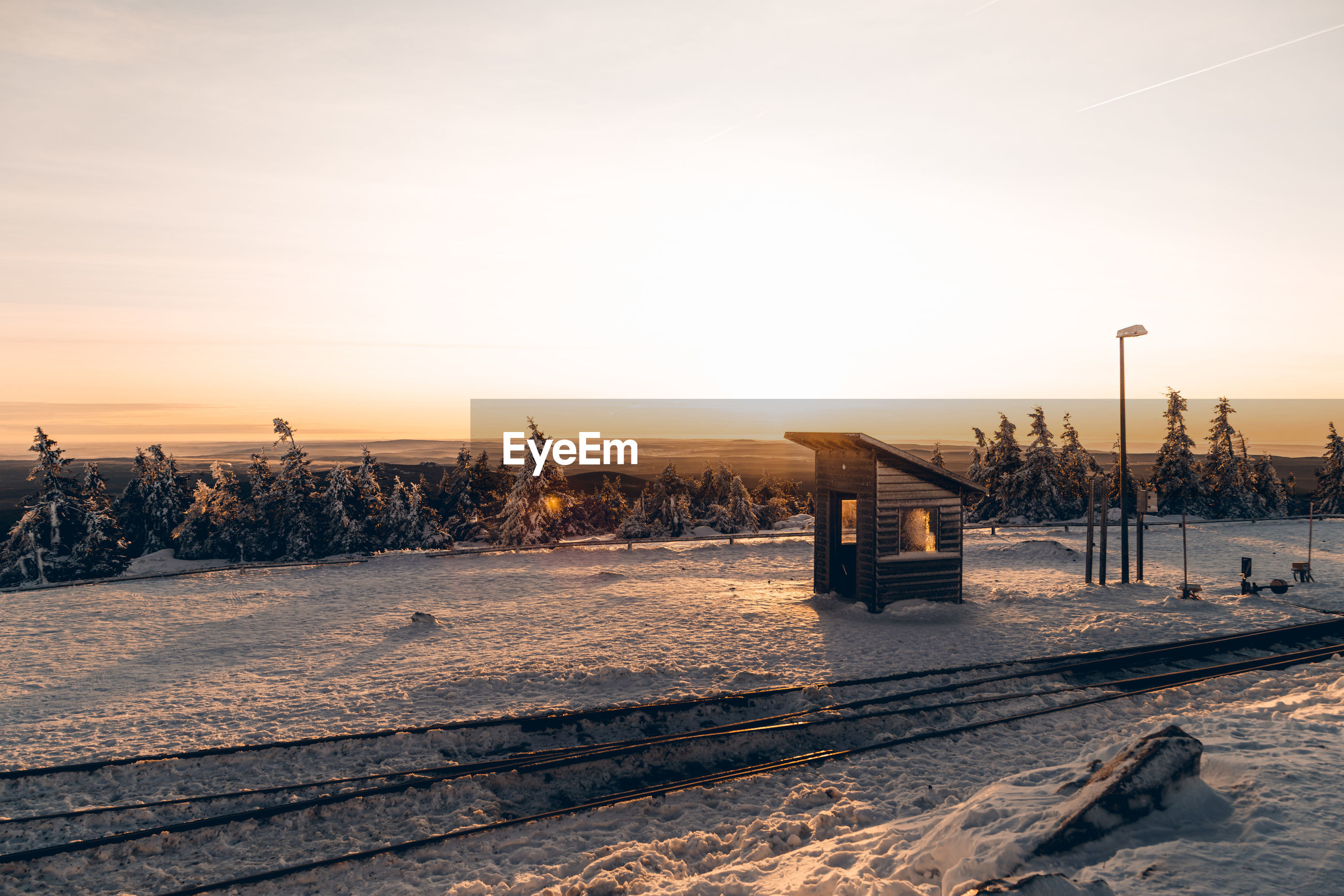 Snow covered railroad tracks against sky during sunset