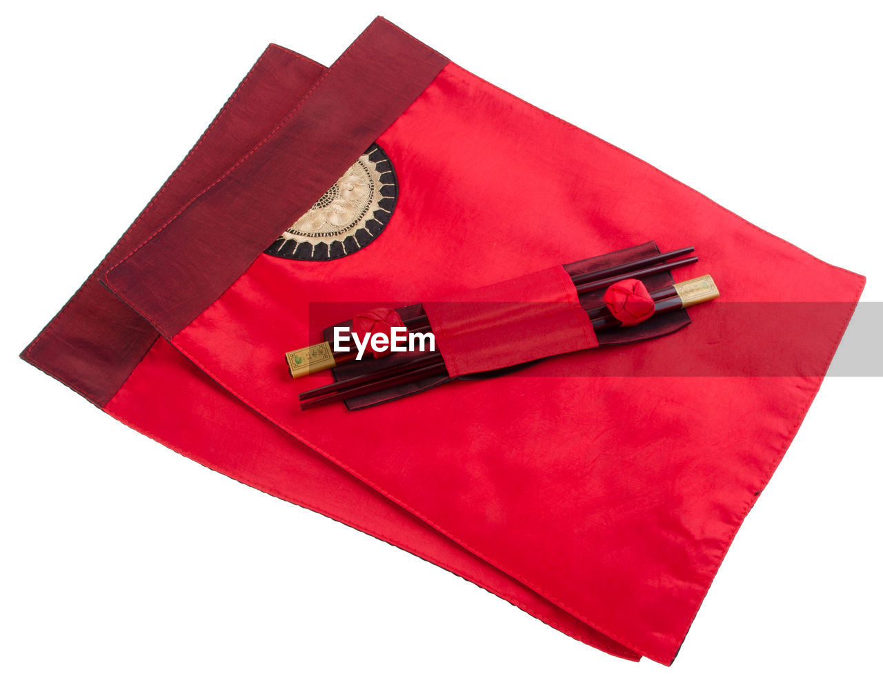 High angle view of chopsticks on red napkins against white background
