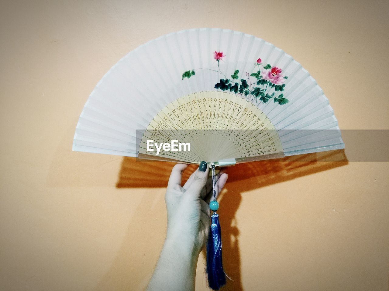 Cropped image of woman hand holding folding fan