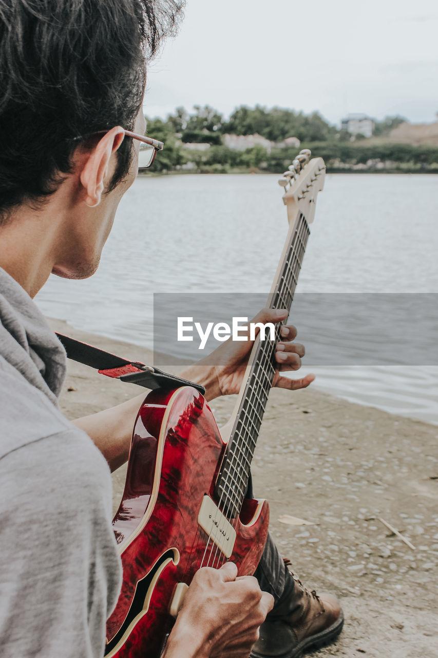 Man playing guitar on riverbank