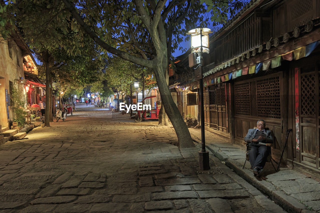 architecture, building exterior, city, street, tree, built structure, men, footpath, plant, building, incidental people, people, real people, direction, the way forward, women, lifestyles, sidewalk, illuminated, adult, outdoors, paving stone