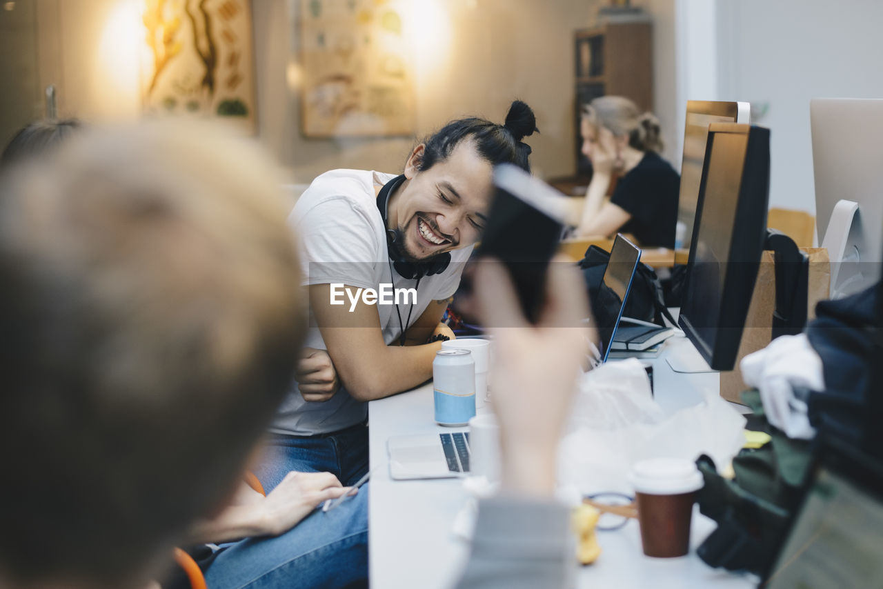 technology, group of people, communication, real people, office, adult, men, computer, table, women, business, males, sitting, young adult, indoors, working, connection, young men, casual clothing, smiling, wireless technology, teamwork, coworker, new business