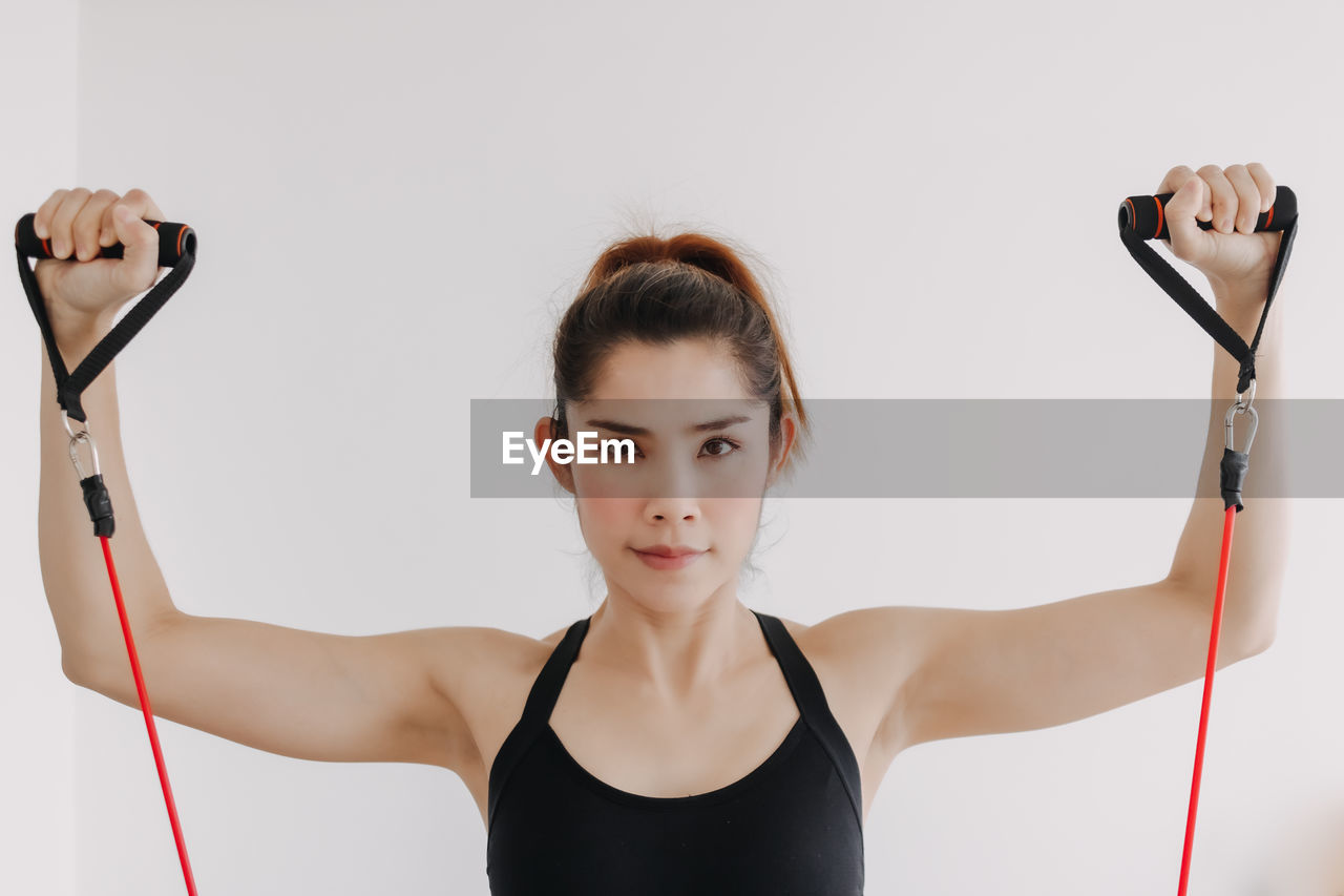 PORTRAIT OF YOUNG WOMAN WITH ARMS RAISED