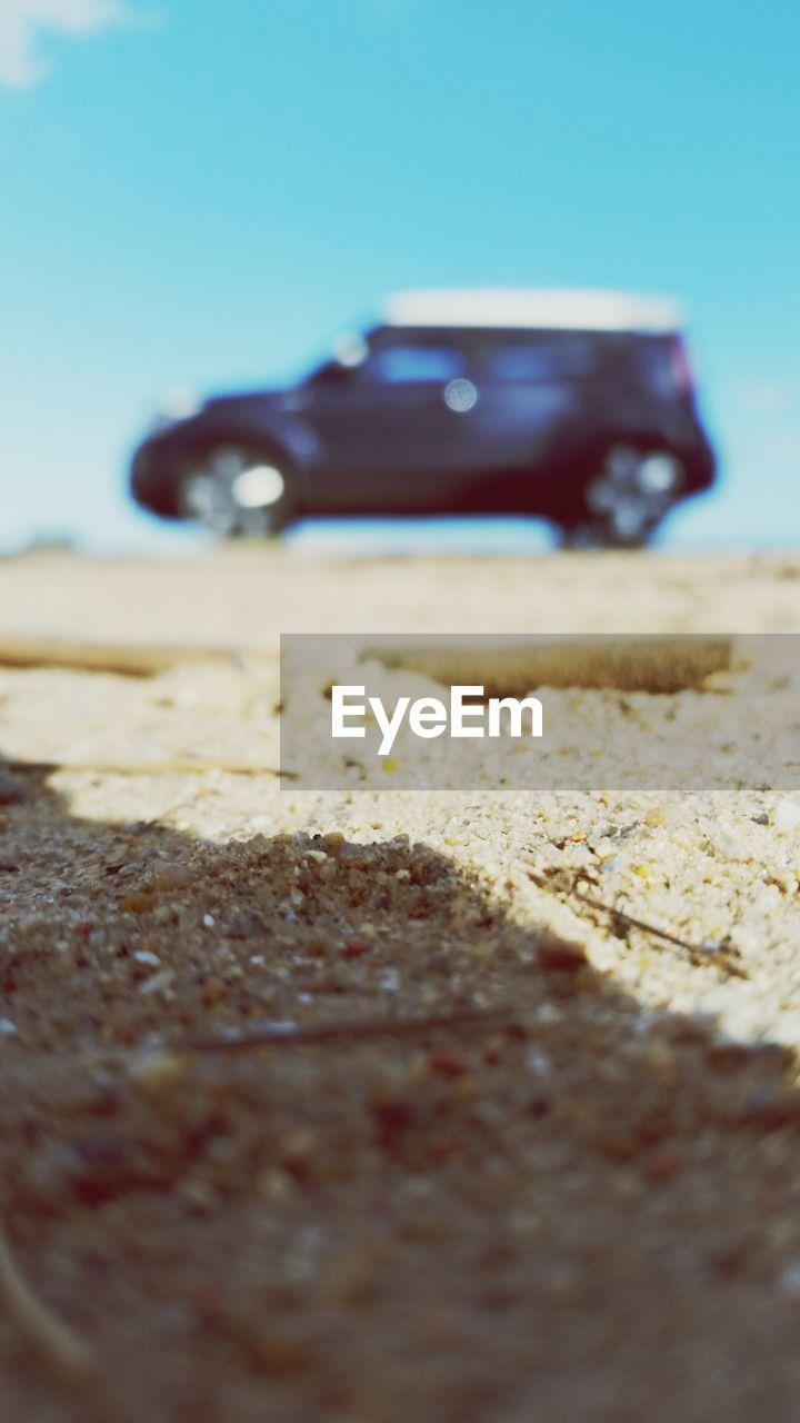 Car Parked On Sand Against Clear Blue Sky