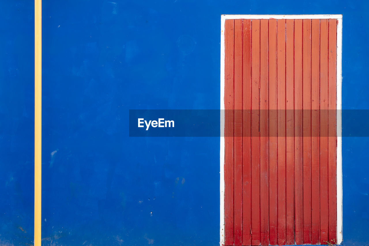 CLOSE-UP OF RED WALL BY BLUE SKY