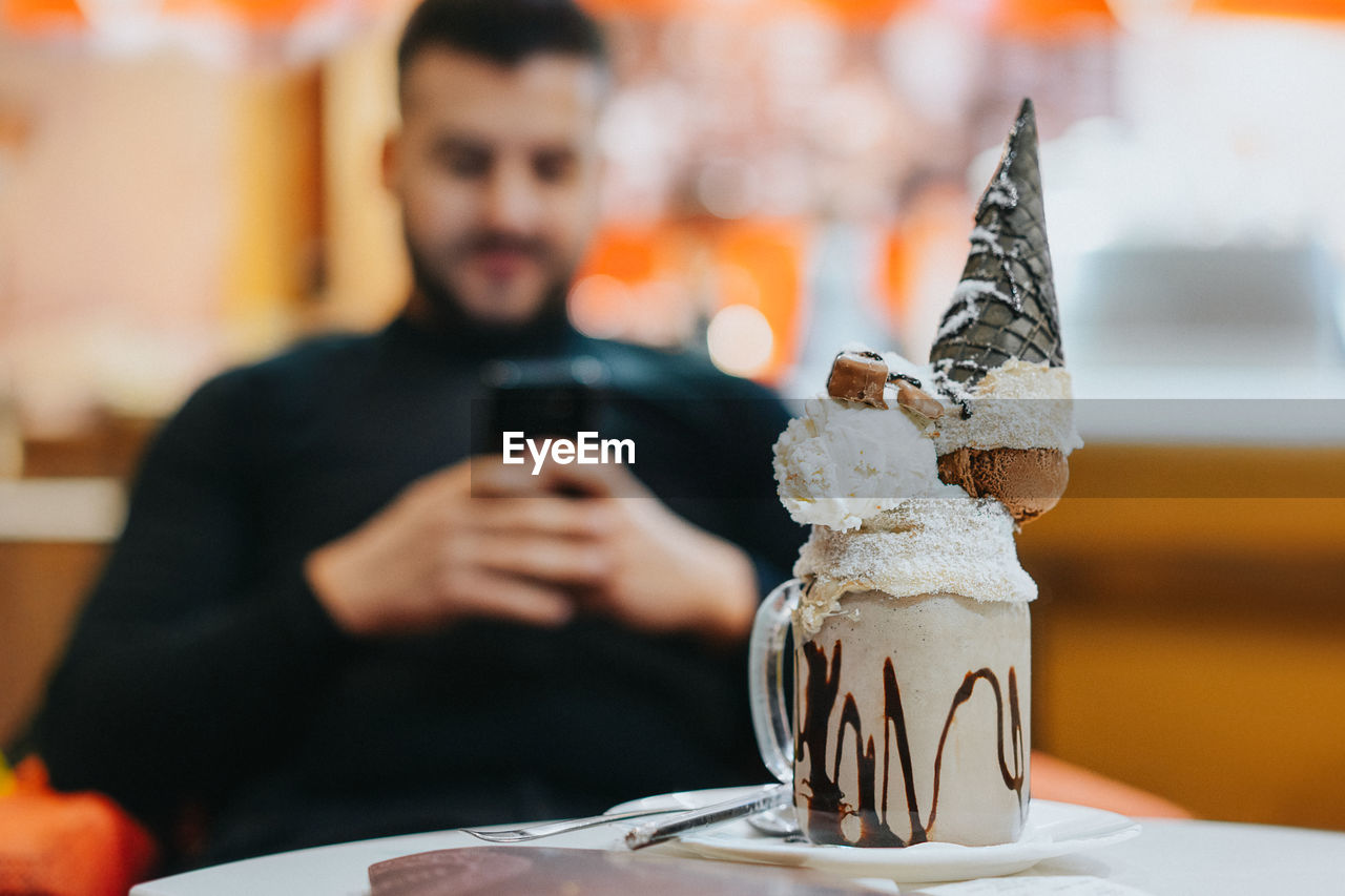 Close-Up Of Dessert Served On Table With Man Using Smart Phone In Background