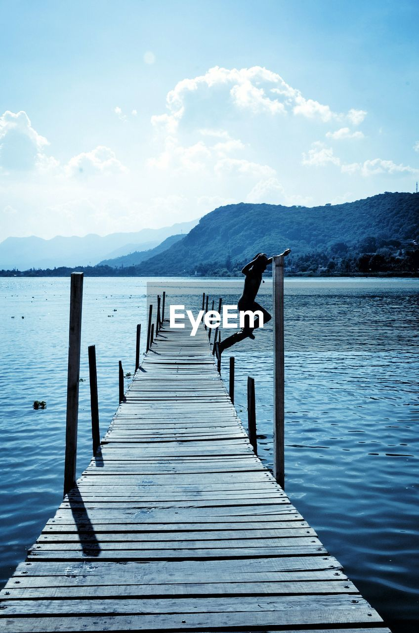 pier, jetty, wood - material, lake, mountain, water, day, wood paneling, nature, outdoors, tranquil scene, beauty in nature, cloud - sky, sky, scenics, real people, mountain range, tranquility, leisure activity, men, one person, wooden post, full length, diving platform, people
