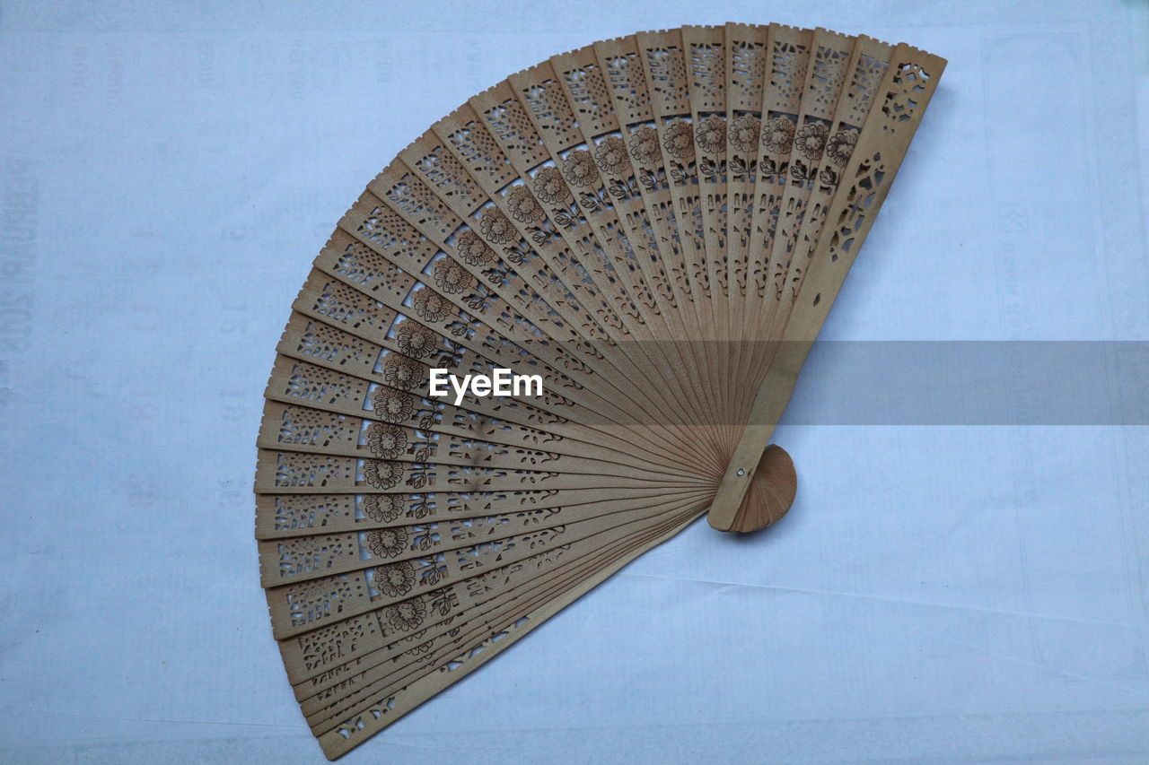 hand fan, no people, pattern, single object, still life, close-up, indoors, wood - material, blue, man made, studio shot, man made object, white color, security, protection, day, art and craft, design, high angle view, foldable, personal accessory