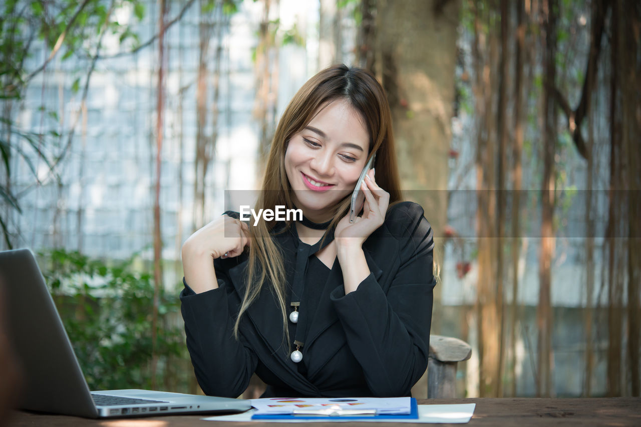 Young woman talking on mobile phone while sitting at table