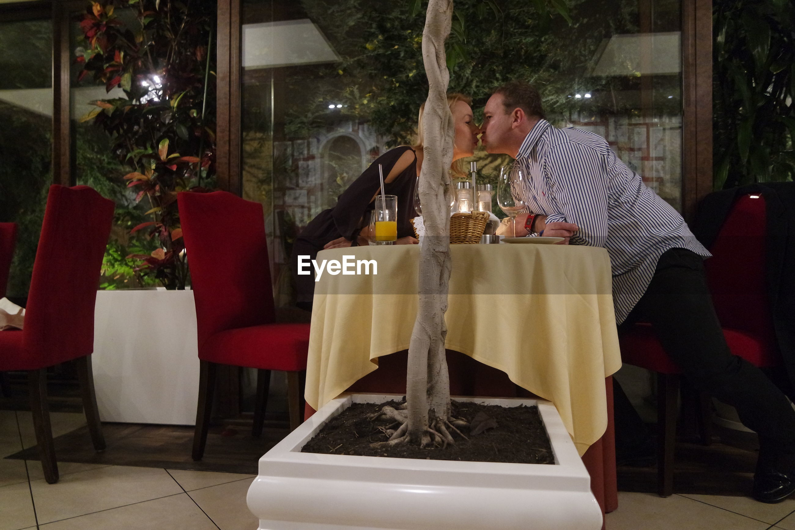 Side view of couple romancing in restaurant
