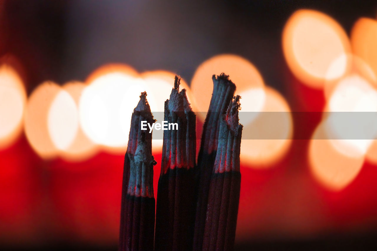 Close-Up Of Incense Sticks Burning At Temple During Night