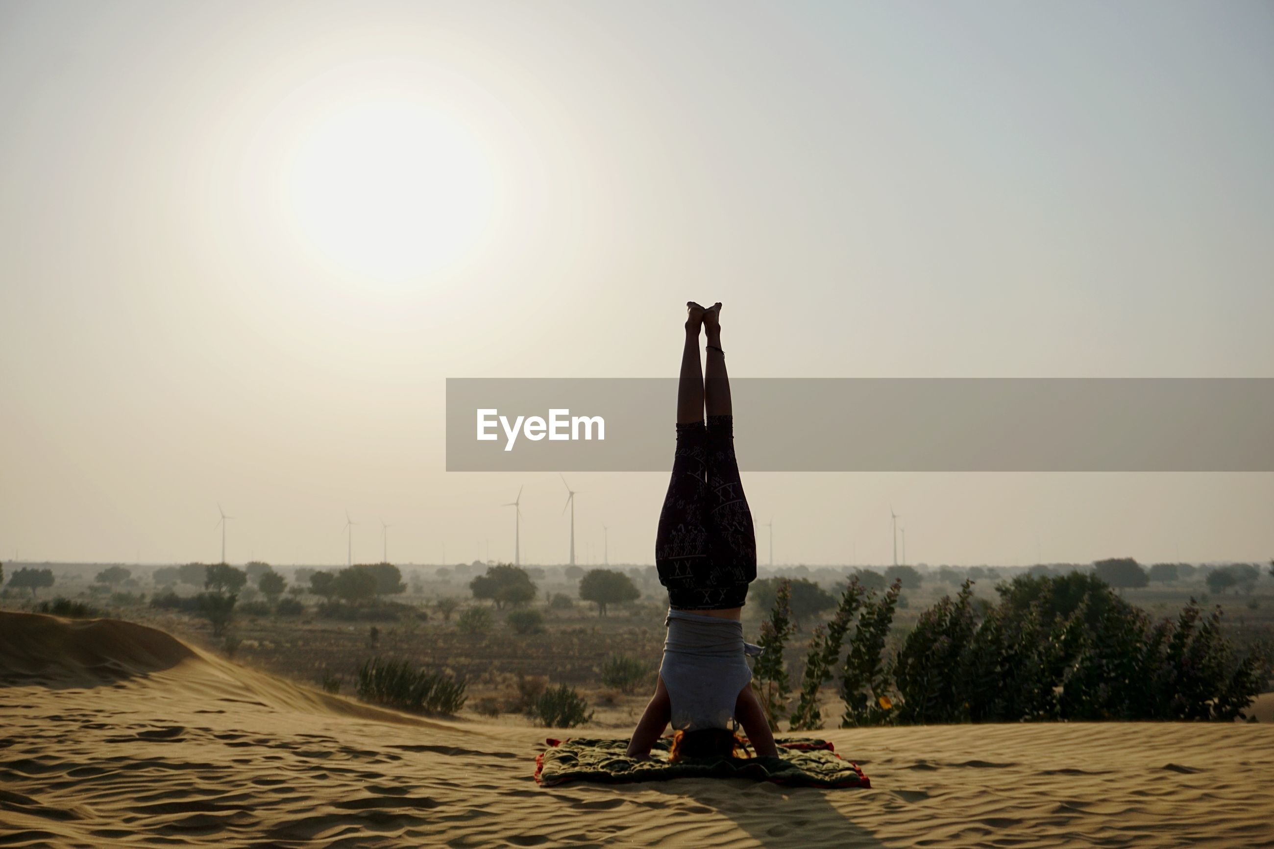 Rear view of woman practicing headstand against sky during sunset