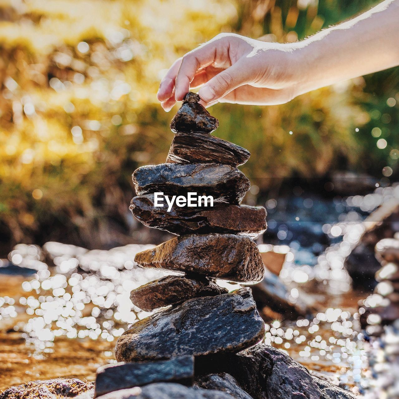 CLOSE-UP OF PERSON STACKING ROCKS