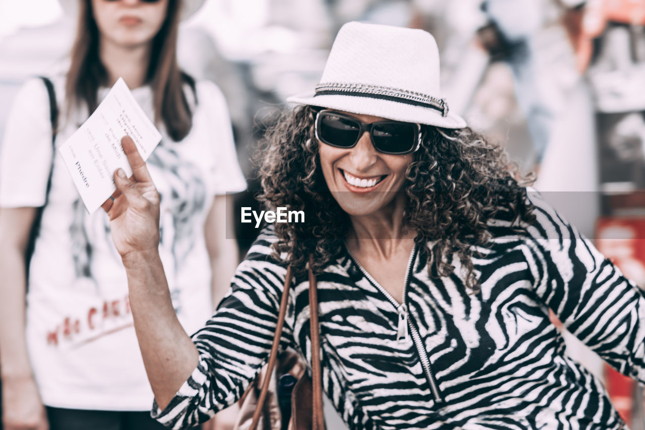 real people, focus on foreground, hat, casual clothing, women, glasses, young adult, adult, clothing, lifestyles, people, smiling, fashion, young women, front view, sunglasses, happiness, holding, leisure activity, incidental people, hairstyle