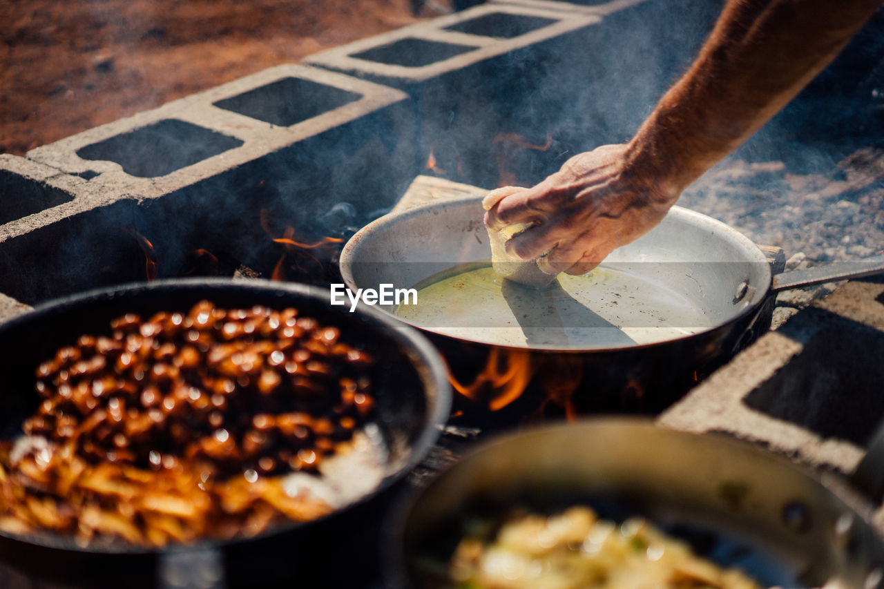 human hand, hand, preparation, food, one person, human body part, food and drink, kitchen utensil, heat - temperature, preparing food, real people, freshness, burning, holding, fire, fire - natural phenomenon, household equipment, close-up, flame, finger