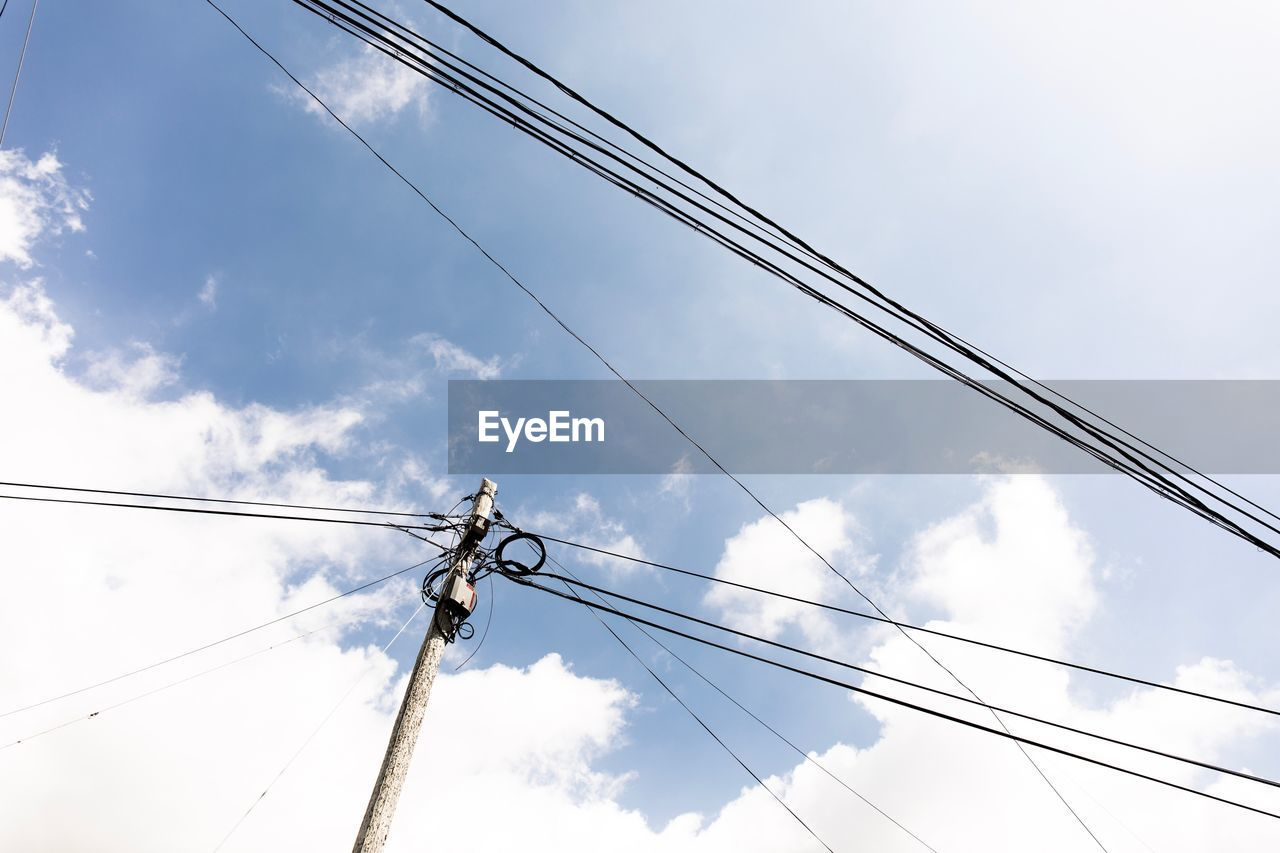 low angle view, cloud - sky, sky, cable, connection, electricity, power line, technology, power supply, day, nature, fuel and power generation, pole, outdoors, no people, complexity, electricity pylon, metal, working, electrical equipment