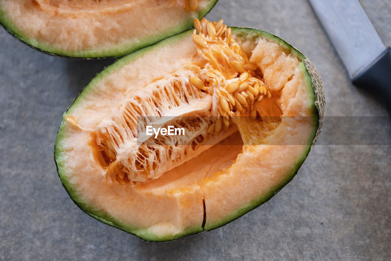 food, food and drink, healthy eating, wellbeing, fruit, freshness, slice, still life, close-up, cross section, no people, indoors, table, high angle view, focus on foreground, melon, seed, ripe, halved, cantaloupe, chopped