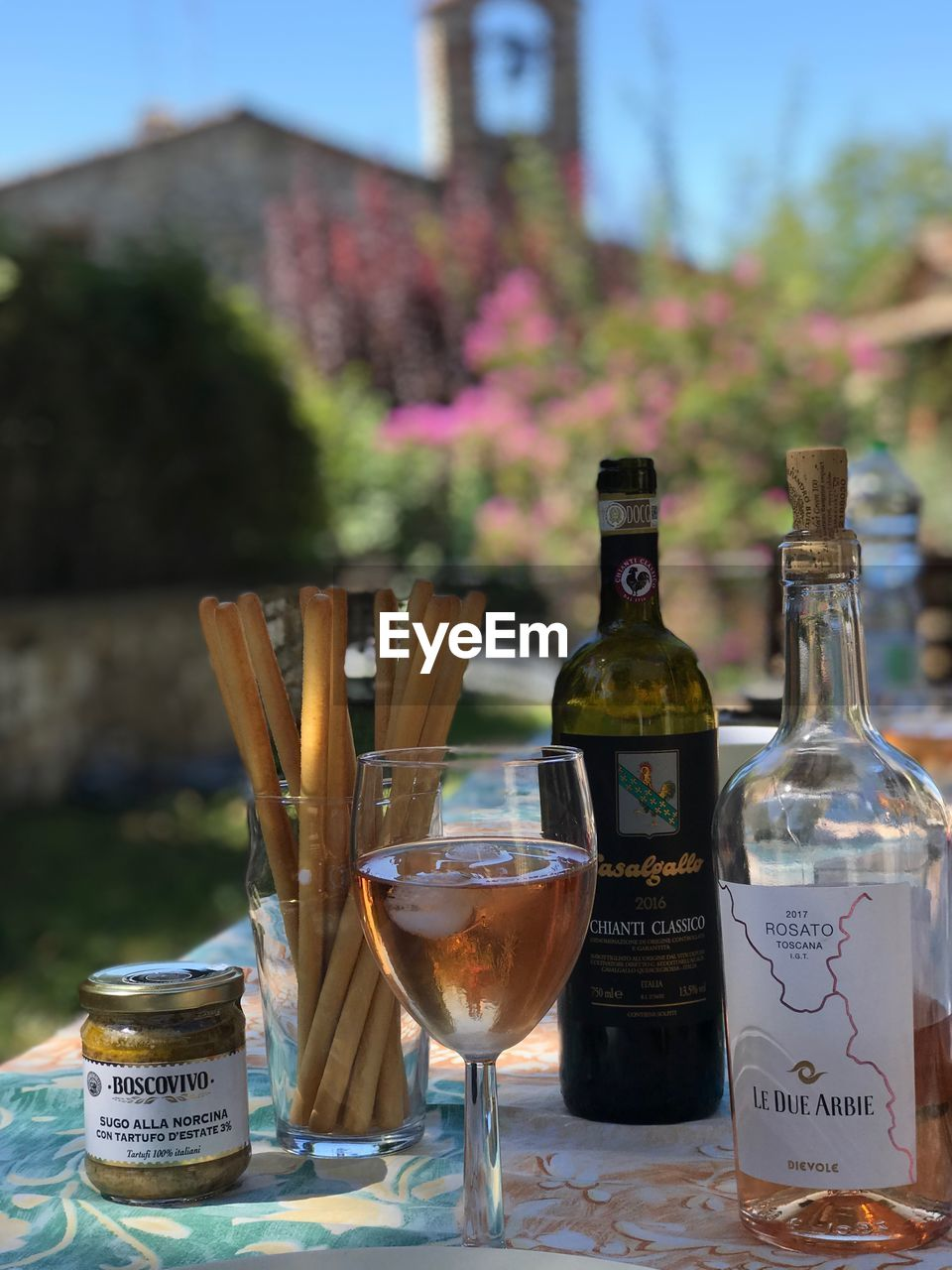 table, container, bottle, drink, alcohol, focus on foreground, food and drink, no people, refreshment, day, glass - material, glass, close-up, nature, still life, transparent, wine, outdoors, text, freshness