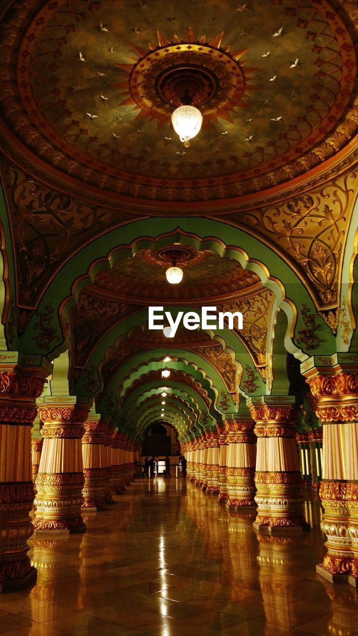 architecture, indoors, illuminated, ceiling, built structure, lighting equipment, arch, architectural column, reflection, building, no people, arcade, corridor, religion, in a row, flooring, place of worship, chandelier, belief, pattern, ornate, mural, tiled floor