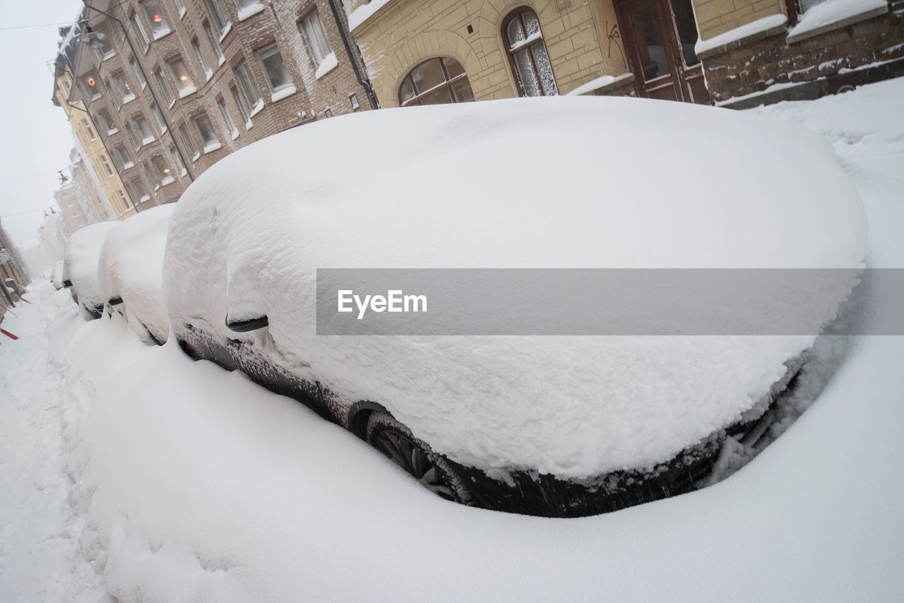 Snowcapped Cars On Street During Winter
