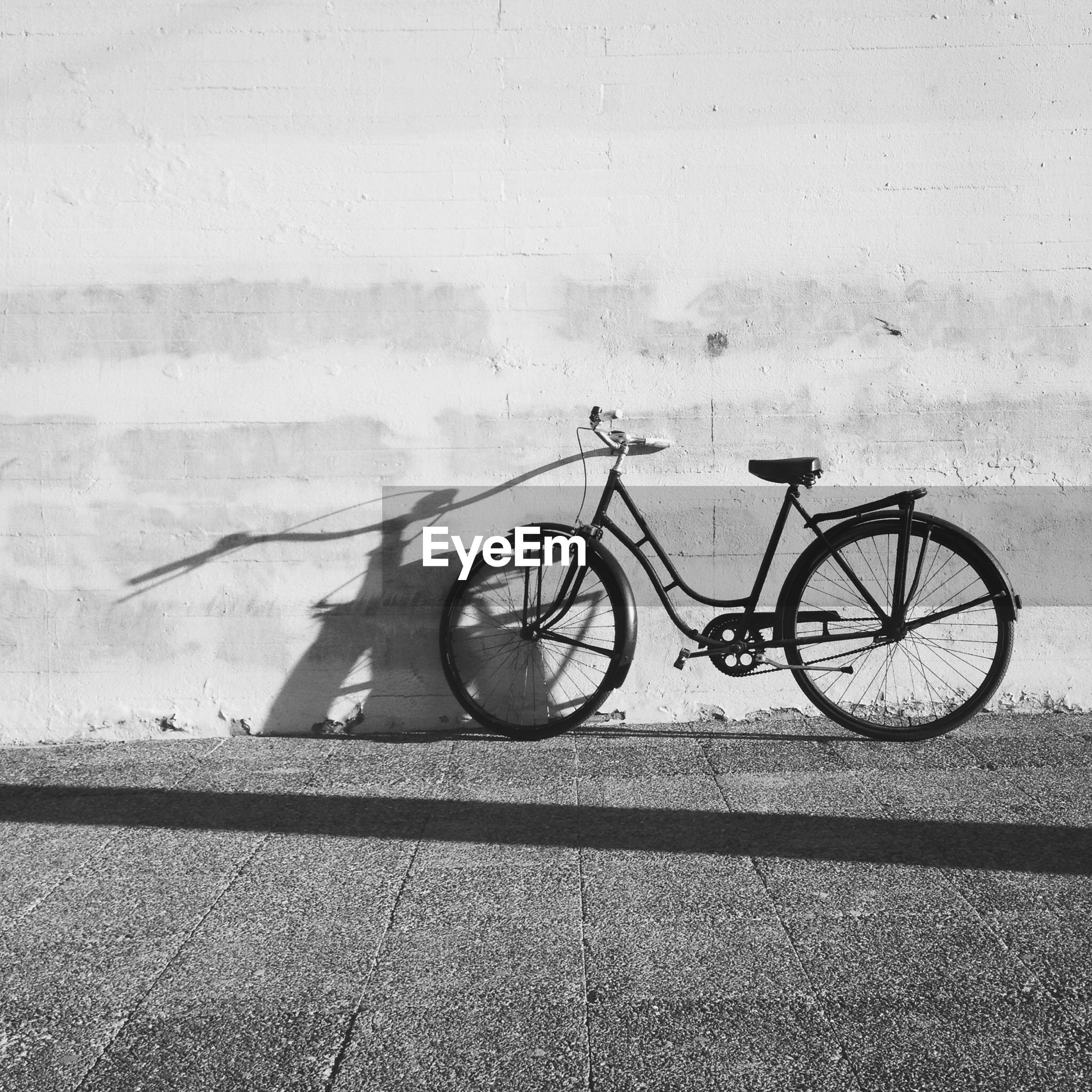 Bicycle parked against wall on street