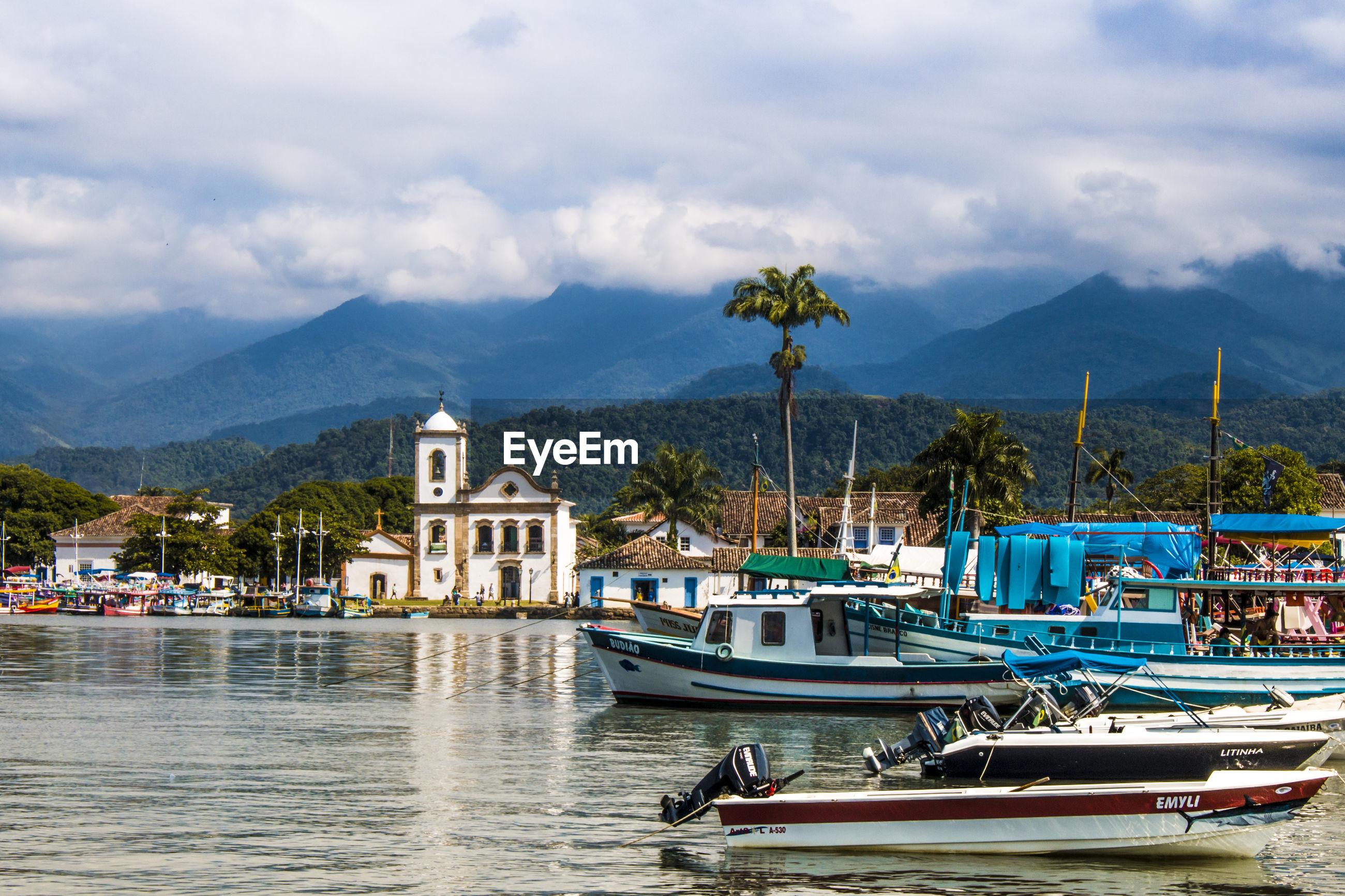 BOATS IN RIVER WITH MOUNTAINS IN BACKGROUND