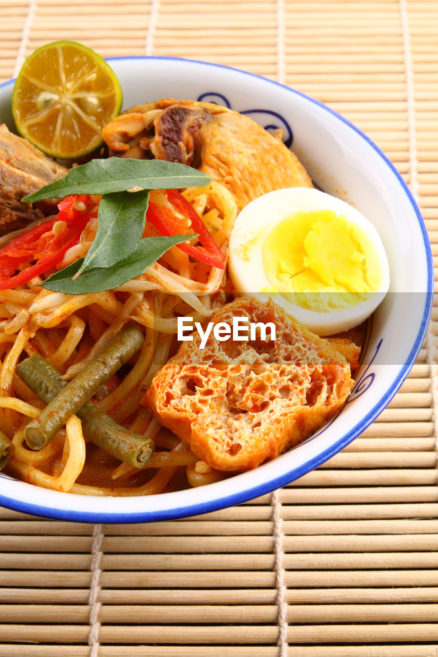 Close-up of noodles soup in bowl on place mat