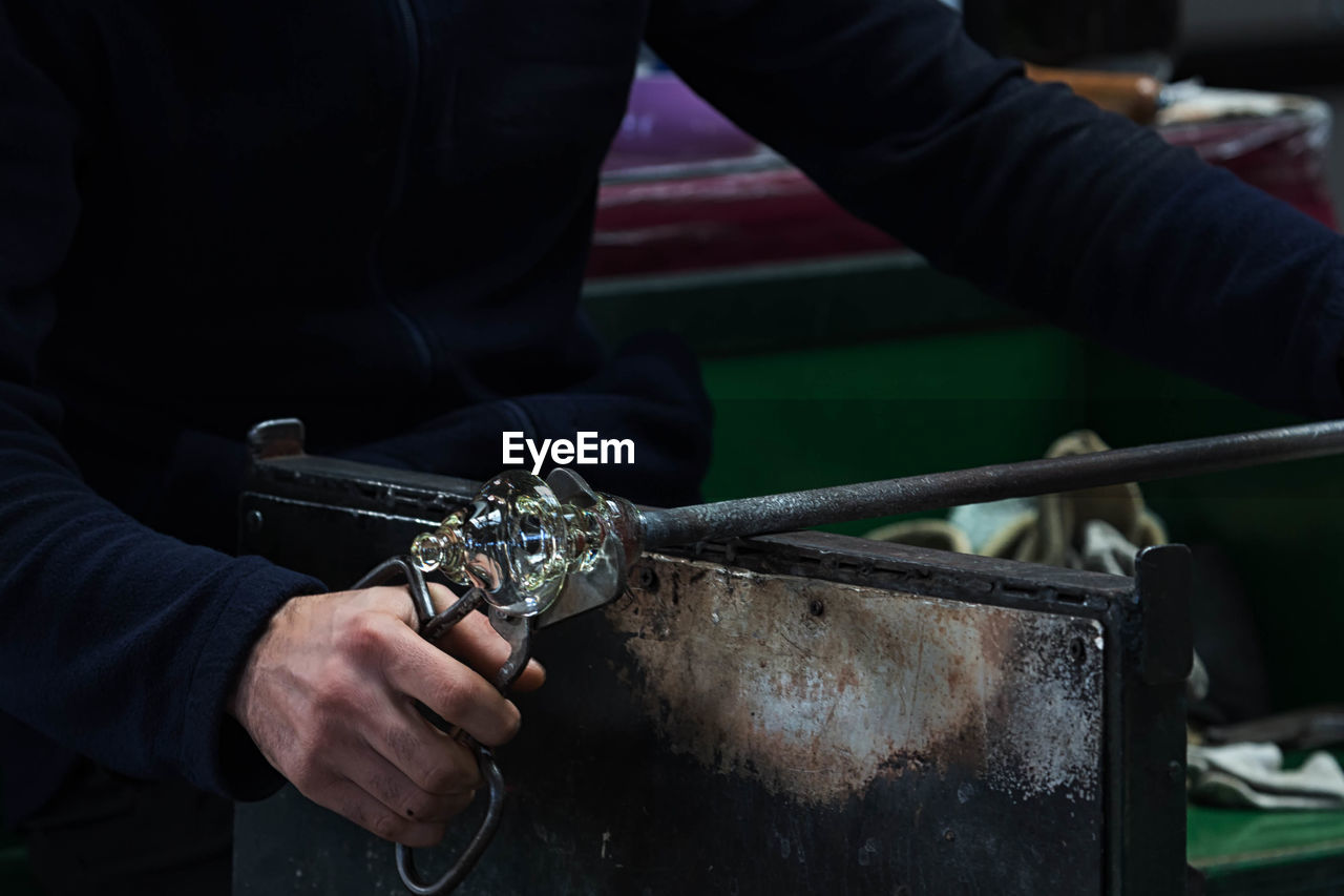 Cropped image of hand holding machine part