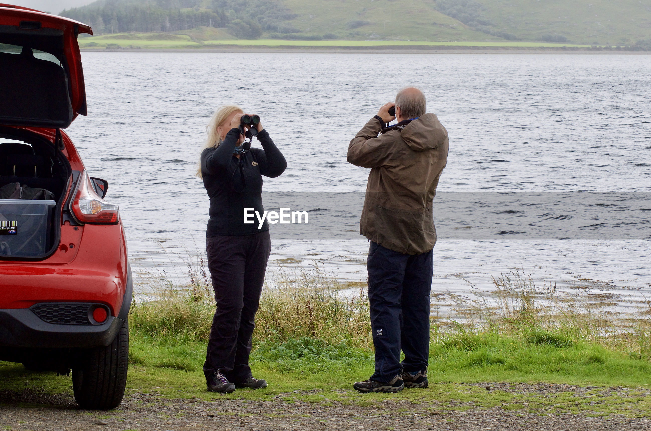 Senior couple looking through binocular while standing on field against lake