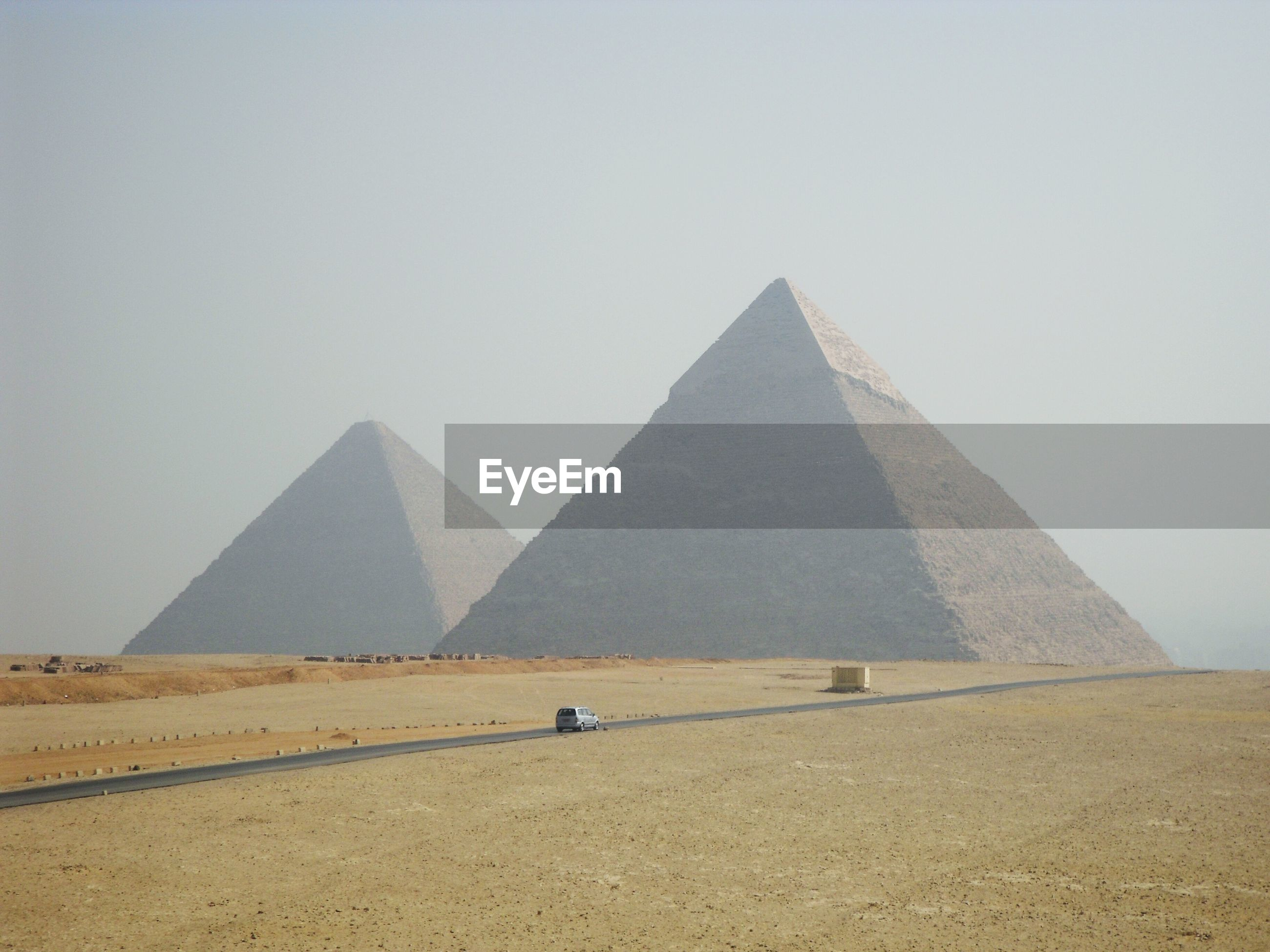 Great pyramid of giza on field against sky