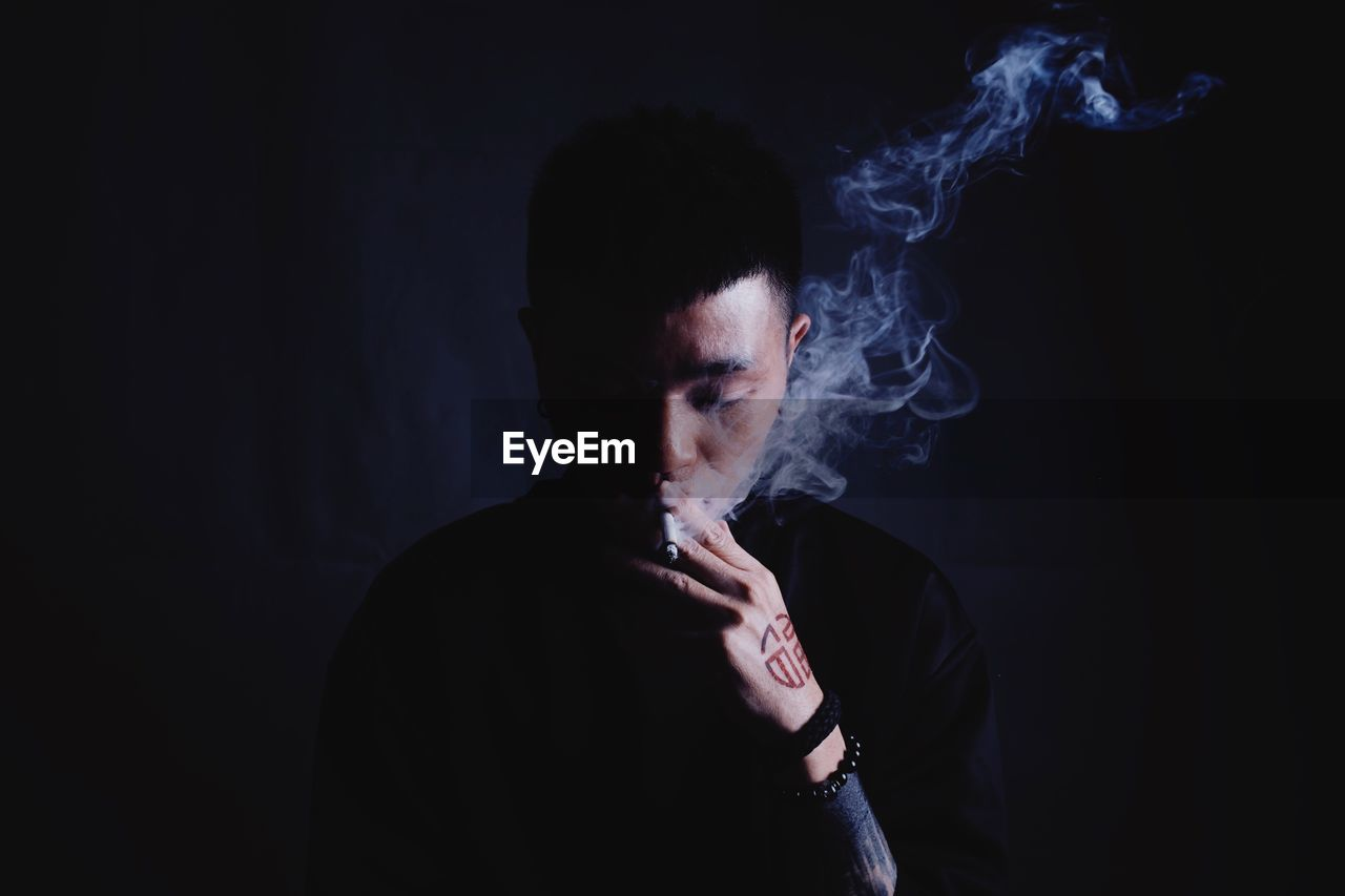 Close-Up Of Man Smoking Cigarette Against Black Background